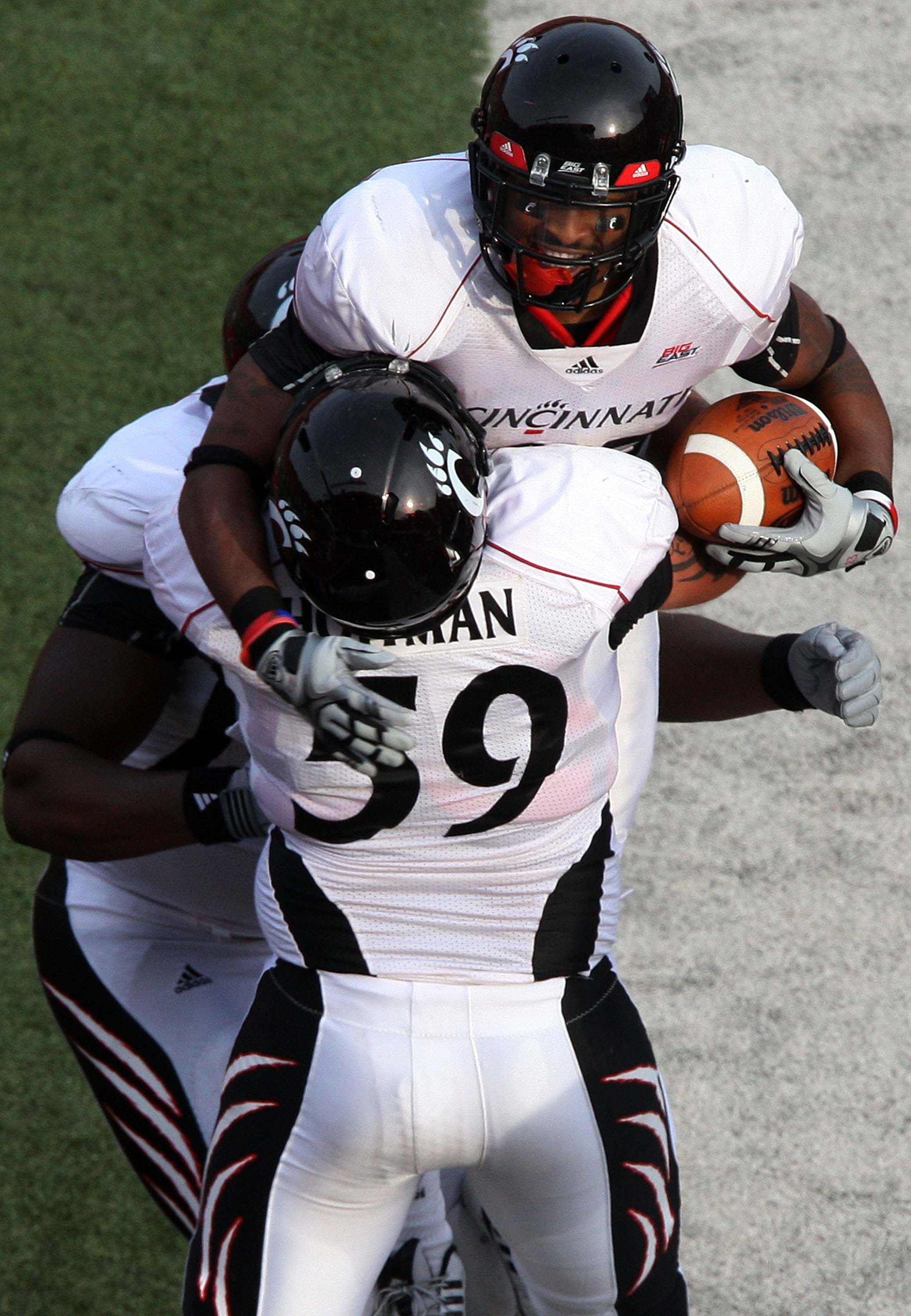 PISCATAWAY, NJ - SEPTEMBER 07:  Isaiah  Pead #23 of the Cincinnati Bearcats celebrates a touchdown against the Rutgers Scarlet Knights with teammate Alex Hoffman #59 at Rutgers Stadium on September 7, 2009 in Piscataway, New Jersey.  (Photo by Jim McIsaac