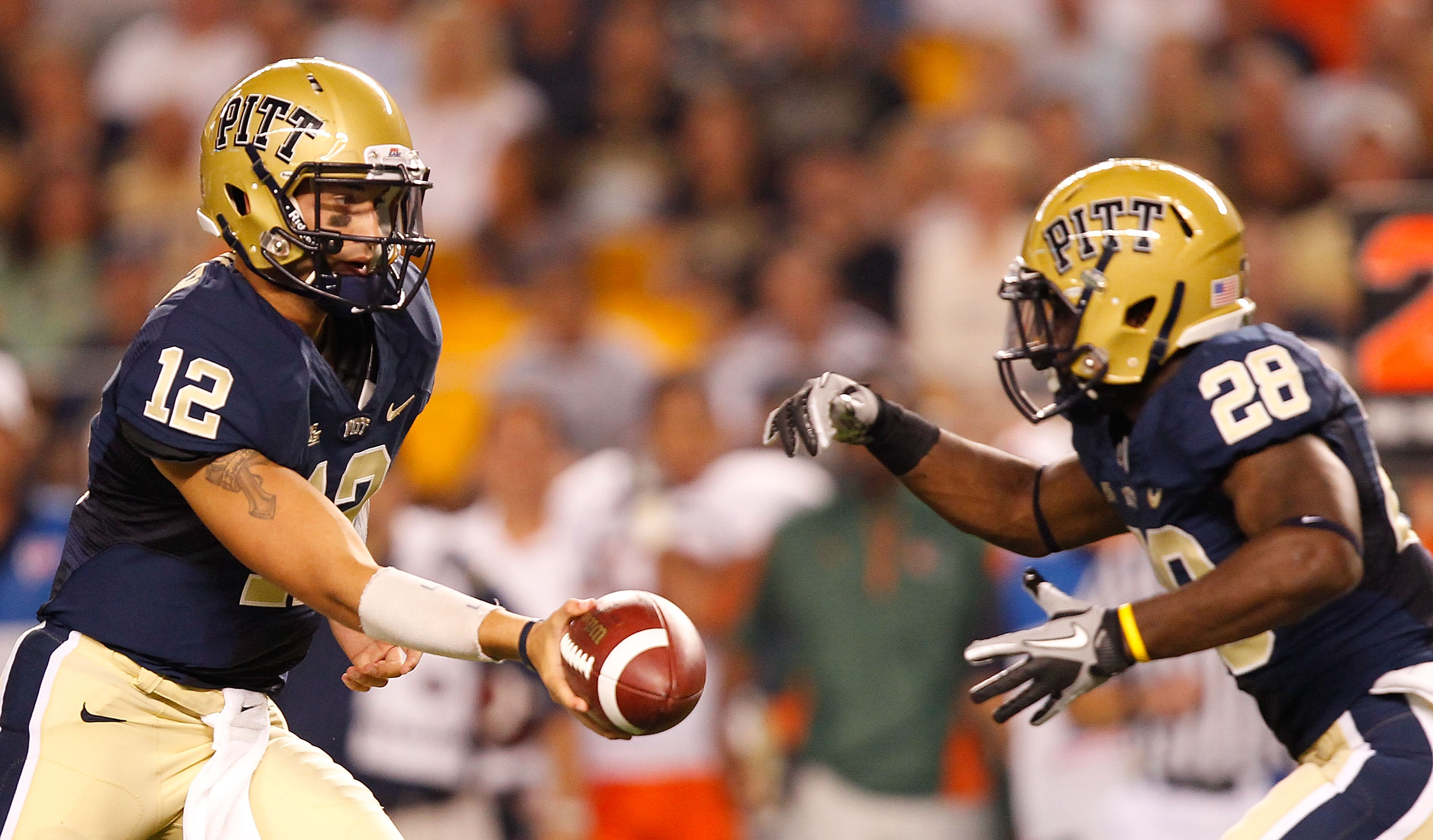 PITTSBURGH - SEPTEMBER 23:  Tino Sunseri #12 of the Pittsburgh Panthers hands the ball off to teammate Dion Lewis #28 during the game against the Miami Hurricanes on September 23, 2010 at Heinz Field in Pittsburgh, Pennsylvania.  (Photo by Jared Wickerham