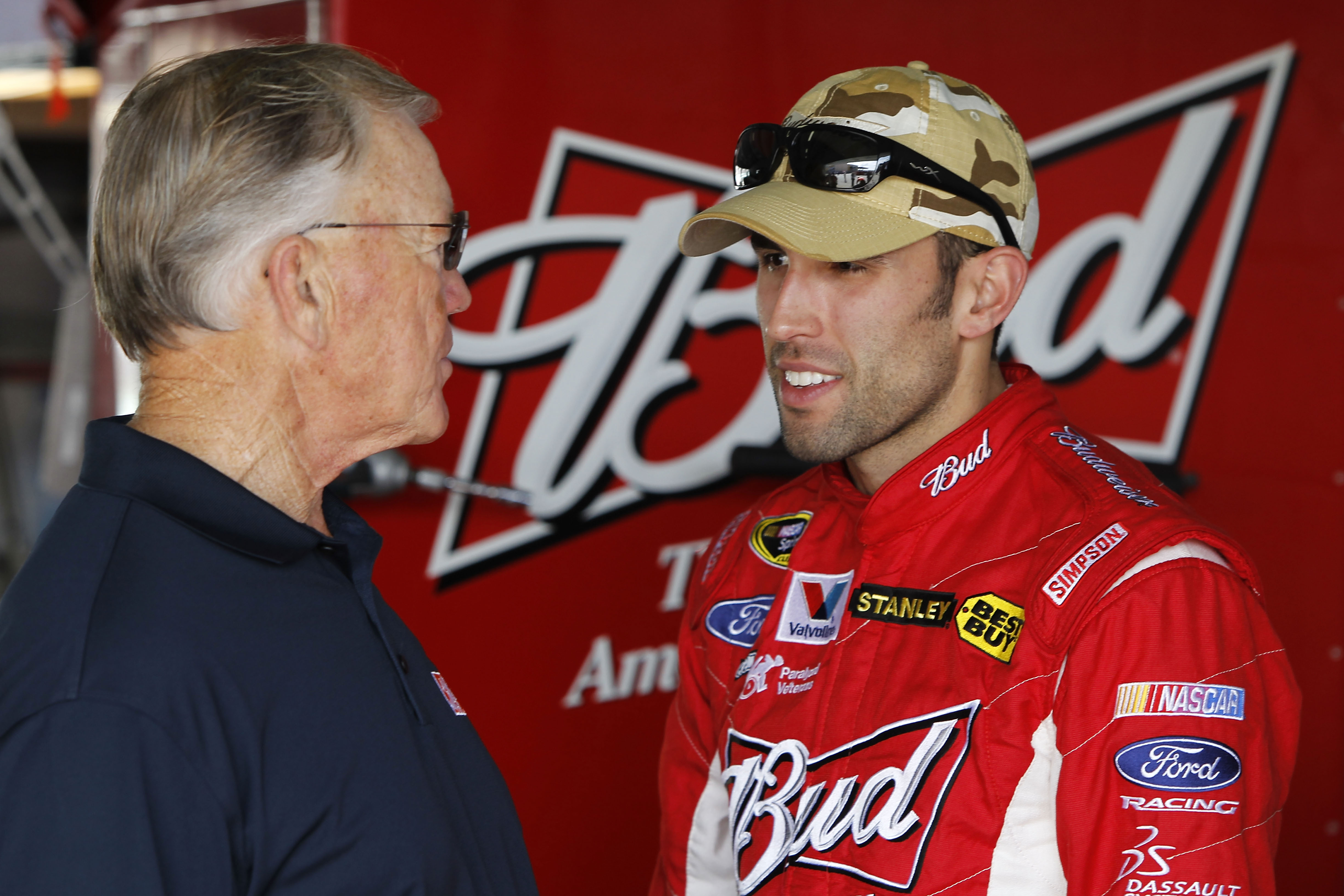 HOMESTEAD, FL - NOVEMBER 20:  Team owner Joe Gibbs (L) talks with Aric Almirola, driver of the #9 Budweiser Ford, in the garage during practice for the NASCAR Sprint Cup Series Ford 400 at Homestead-Miami Speedway on November 20, 2010 in Homestead, Florid