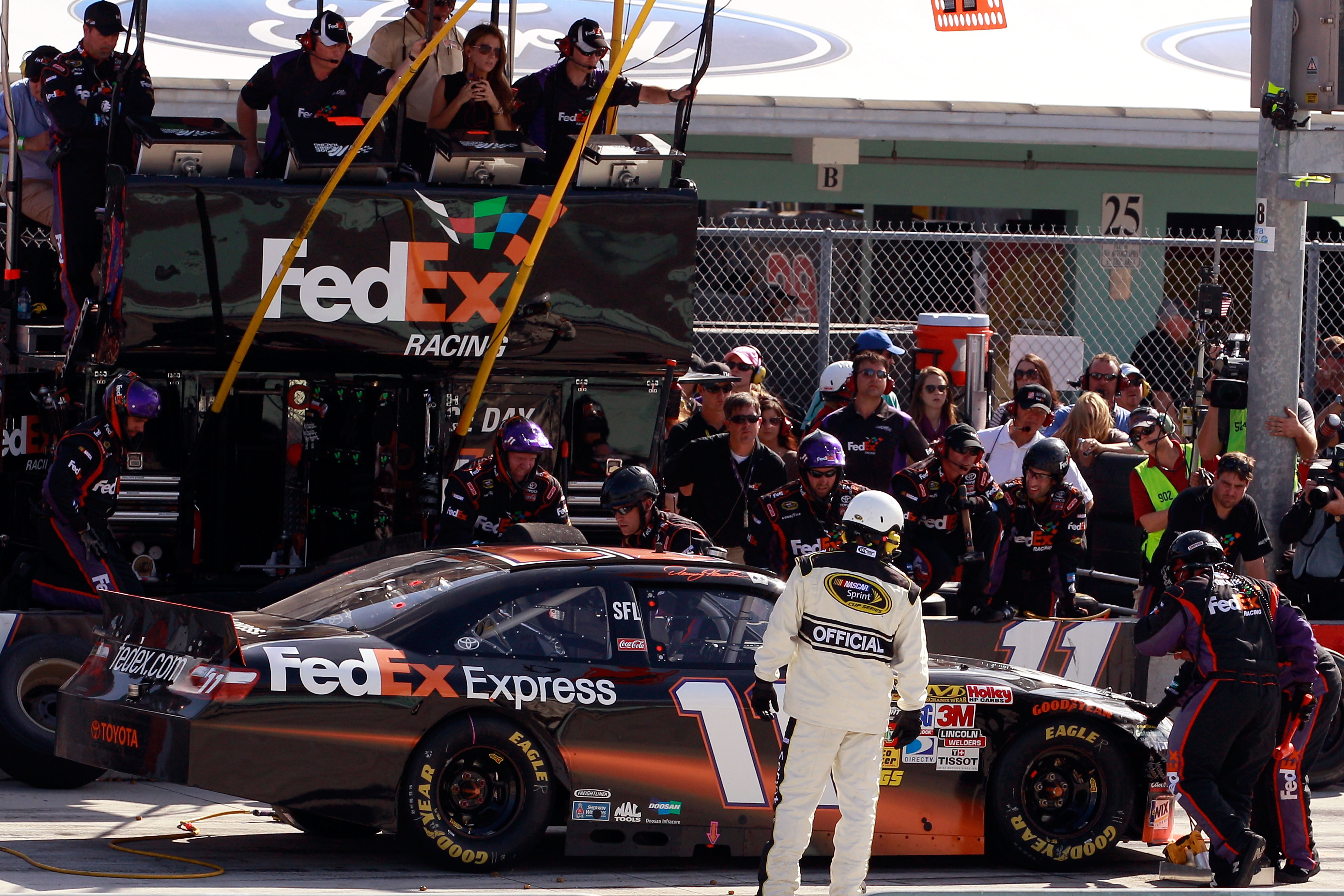 HOMESTEAD, FL - NOVEMBER 21:  Denny Hamlin, driver of the #11 FedEx Toyota, makes a pit stop after sustaining front end damage during the NASCAR Sprint Cup Series Ford 400 at Homestead-Miami Speedway on November 21, 2010 in Homestead, Florida.  (Photo by