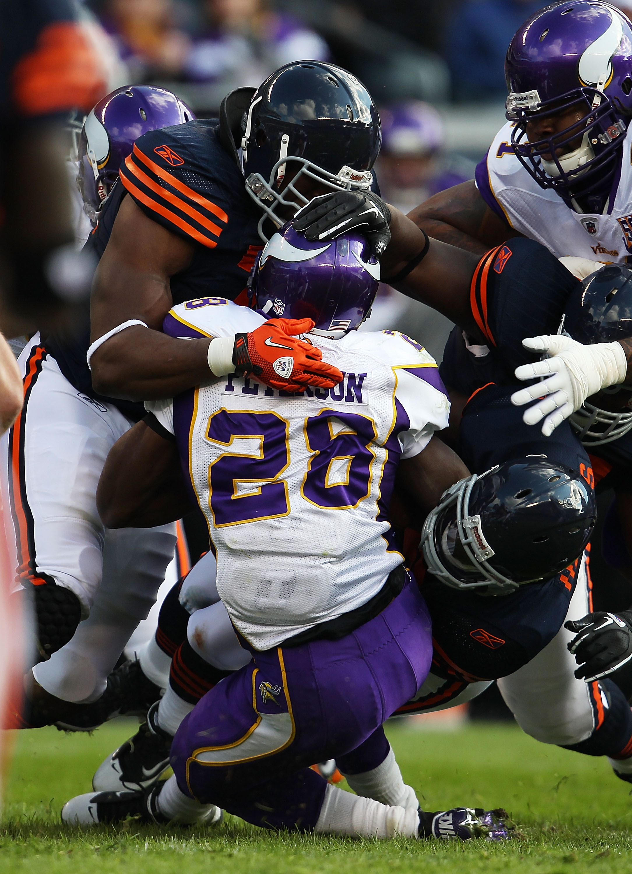 CHICAGO - NOVEMBER 14: Adrian Peterson #28 of the Minnesota Vikings is tackled by members of the Chicago Bear defense including Israel Idonije #71 (L) and Chris Harris #46 at Soldier Field on November 14, 2010 in Chicago, Illinois. The Bears defeated the