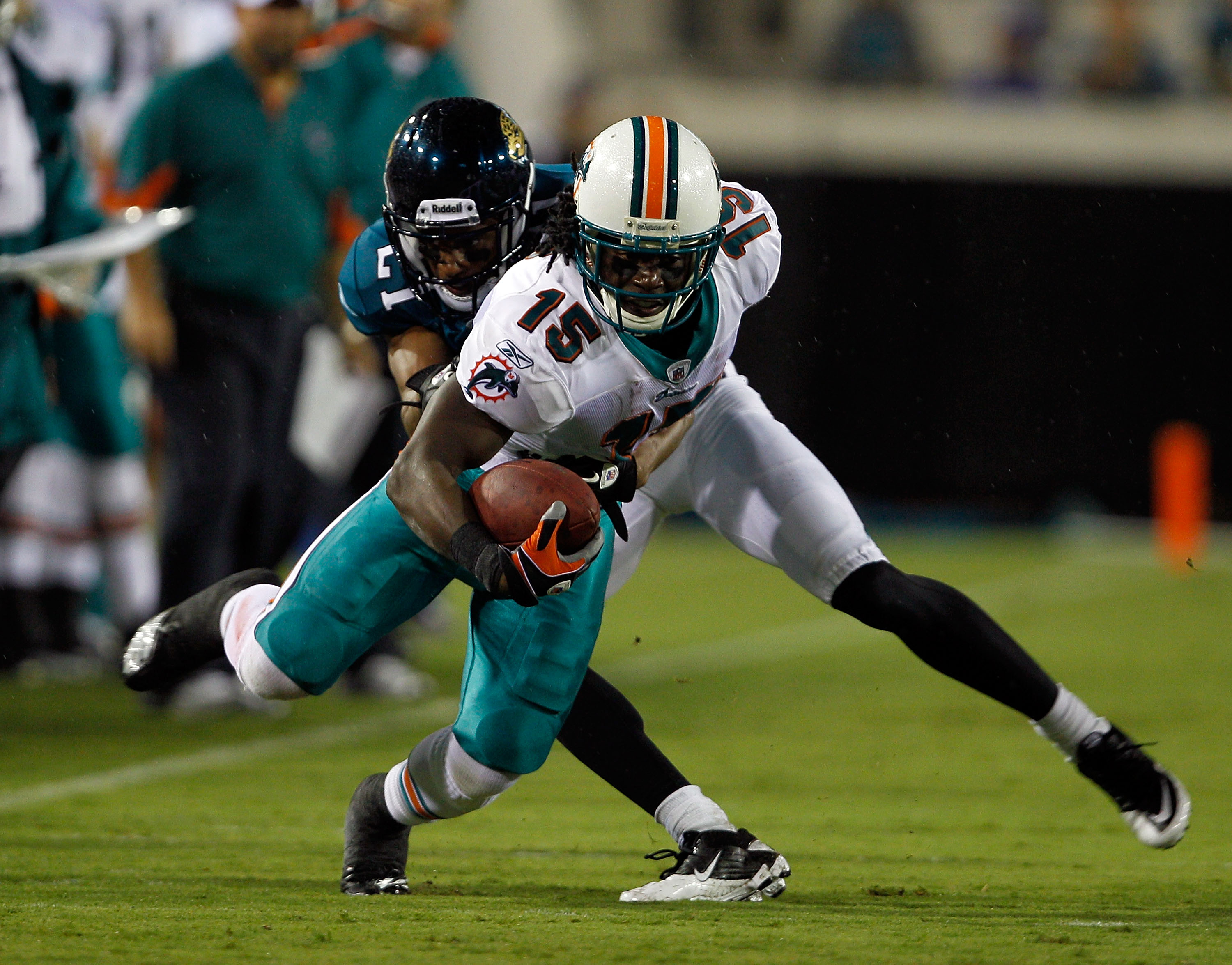 JACKSONVILLE, FL - AUGUST 21:  Derek Cox #21 of the Jacksonville Jaguars attempts to tackle Davone Bess #15 of the Miami Dolphins during the preseason game at EverBank Field on August 21, 2010 in Jacksonville, Florida.  (Photo by Sam Greenwood/Getty Image