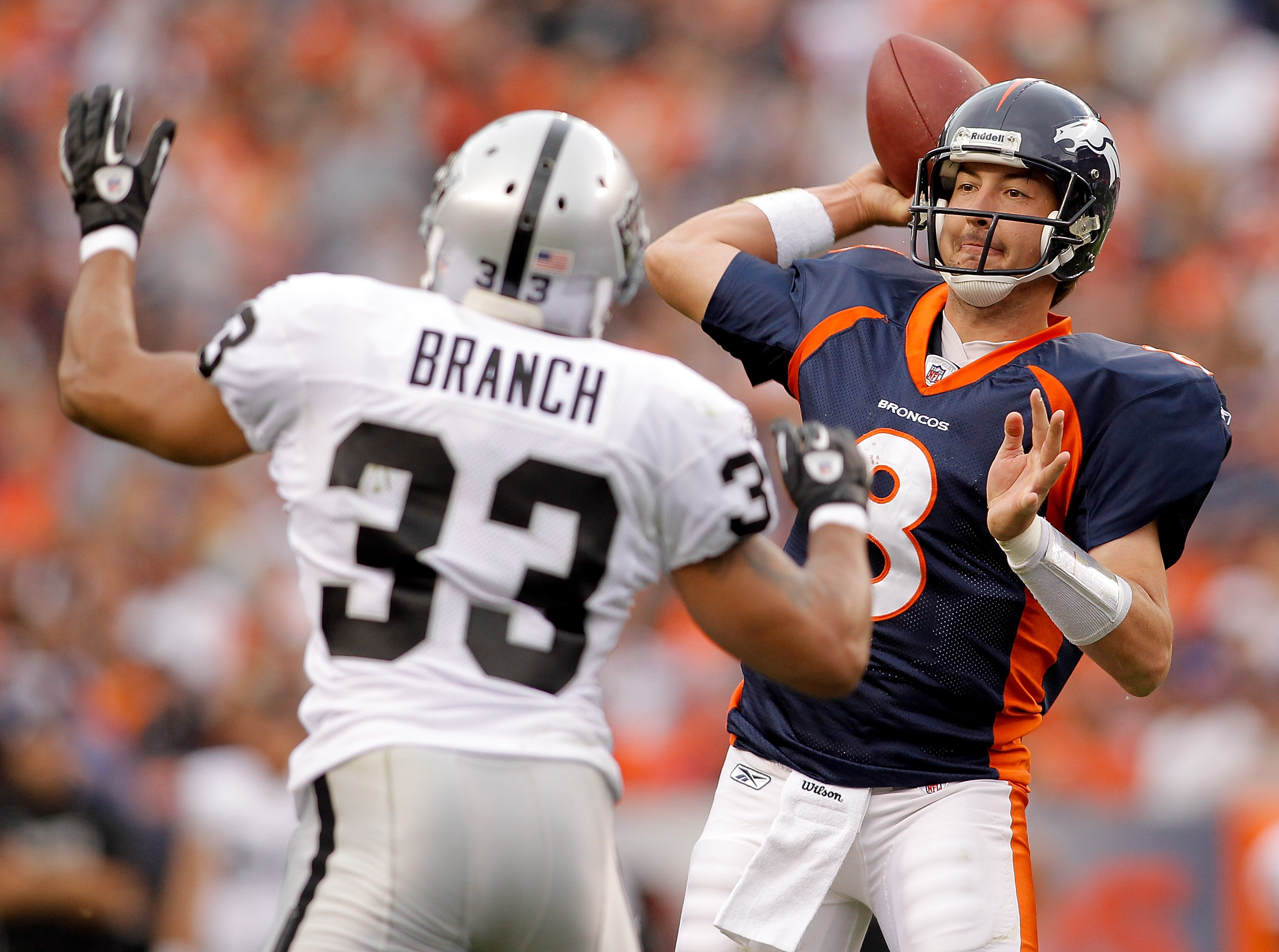 DENVER - OCTOBER 24:  Quarterback Kyle Orton #8 of the Denver Broncos makes a pass in front of safety Tyvon Branch #33 of the Oakland Raiders in the second quarter at INVESCO Field at Mile High on October 24, 2010 in Denver, Colorado. (Photo by Justin Edm
