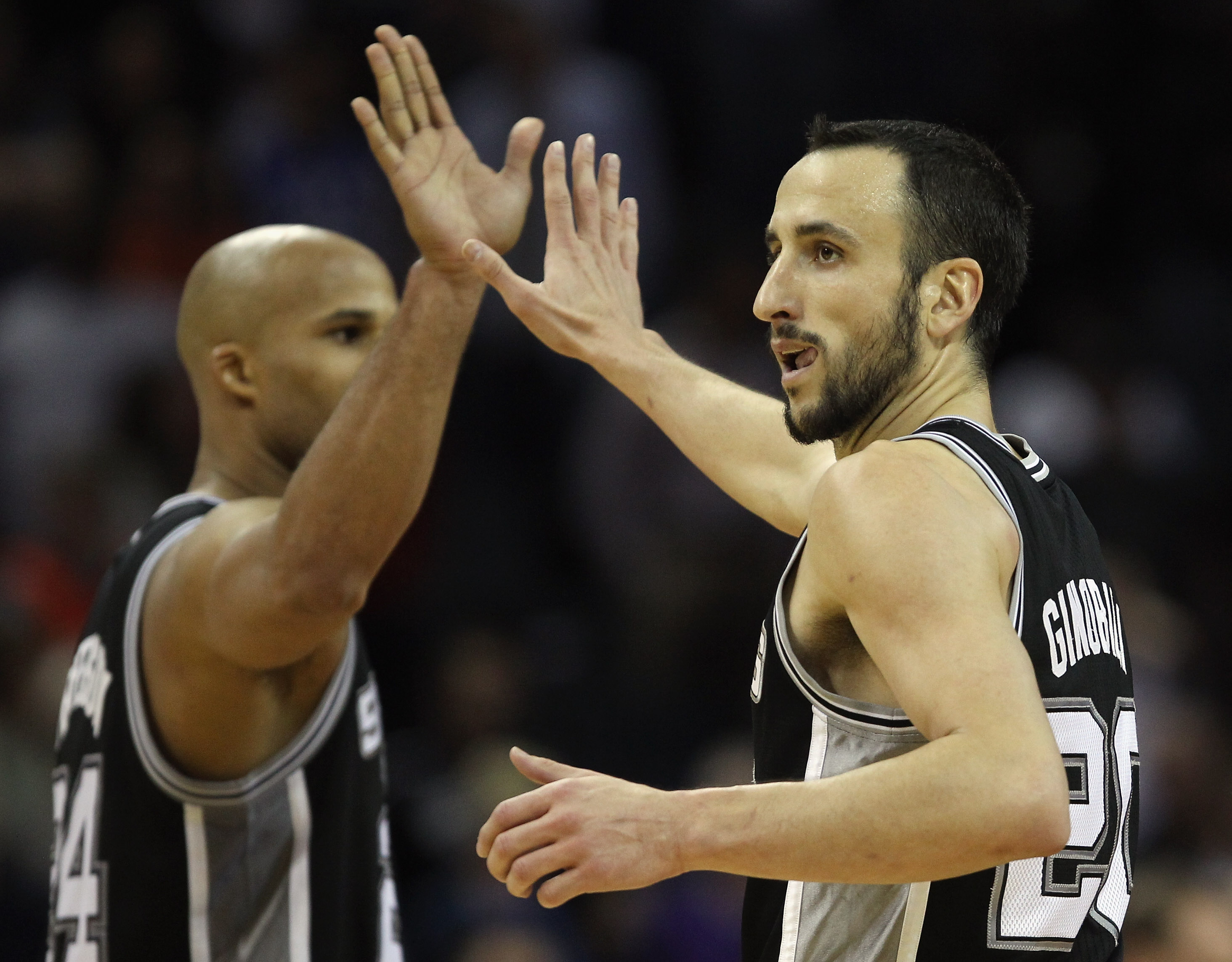 CHARLOTTE, NC - NOVEMBER 08:  Manu Ginobili #20 of the San Antonio Spurs celebrates with teammate Richard Jefferson #24 after making a basket late in the 4th quarter giving the Spurs a 95-91 victory over the Charlotte Bobcats during their game at Time War