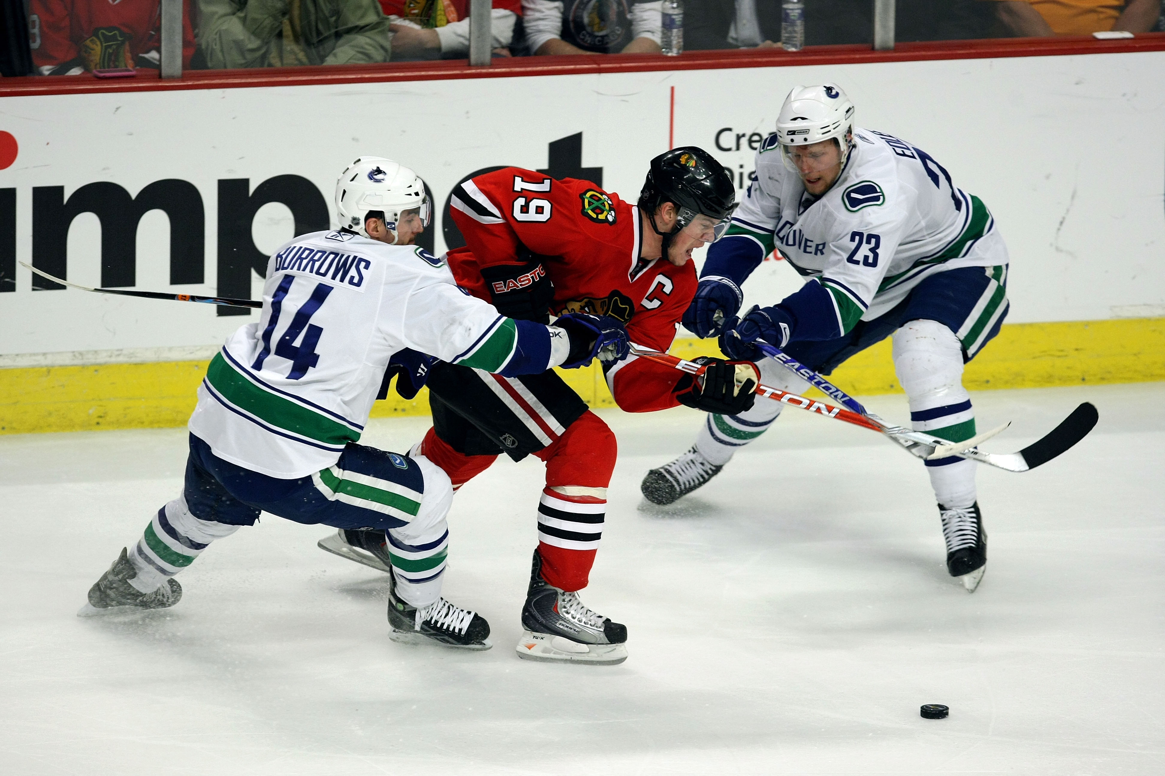 CHICAGO - MAY 11:  Jonathan Toews #19 of the Chicago Blackhawks fights for the puck against Alex Burrows #14 and Alexander Edler #23 of the Vancouver Canucks during Game Six of the Western Conference Semifinal Round of the 2009 Stanley Cup Playoffs on May