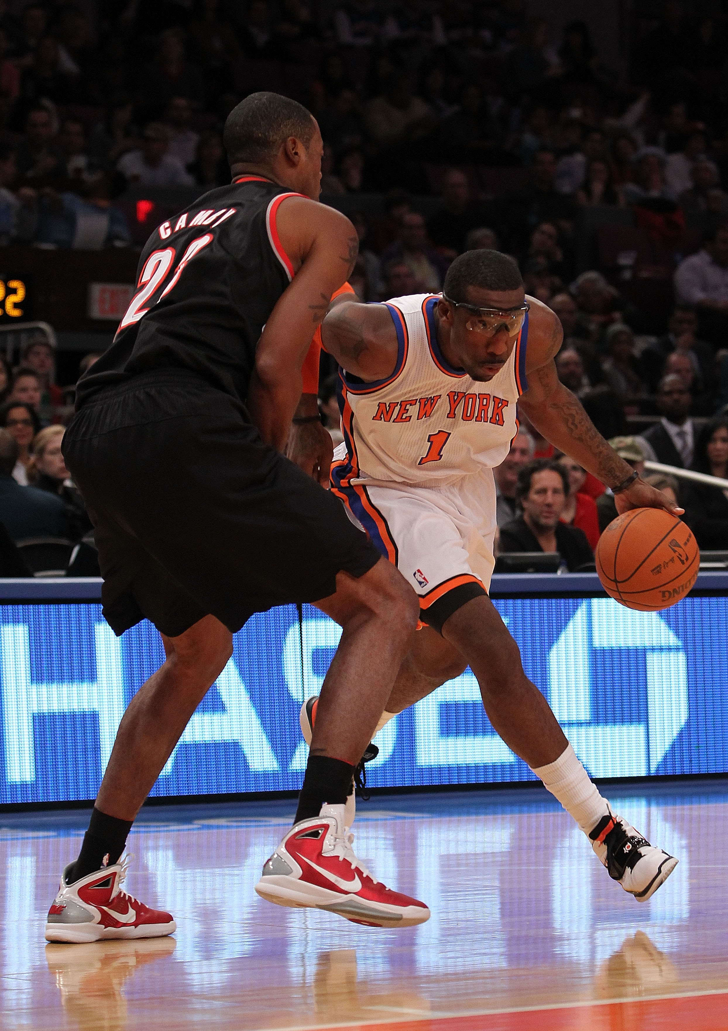 NEW YORK - OCTOBER 30:  Amar'e Stoudemire #1 of the New York Knicks drives against Marcus Camby #23 of the Portland Trail Blazers at Madison Square Garden on October 30, 2010 in New York City. NOTE TO USER: User expressly acknowledges and agrees that, by