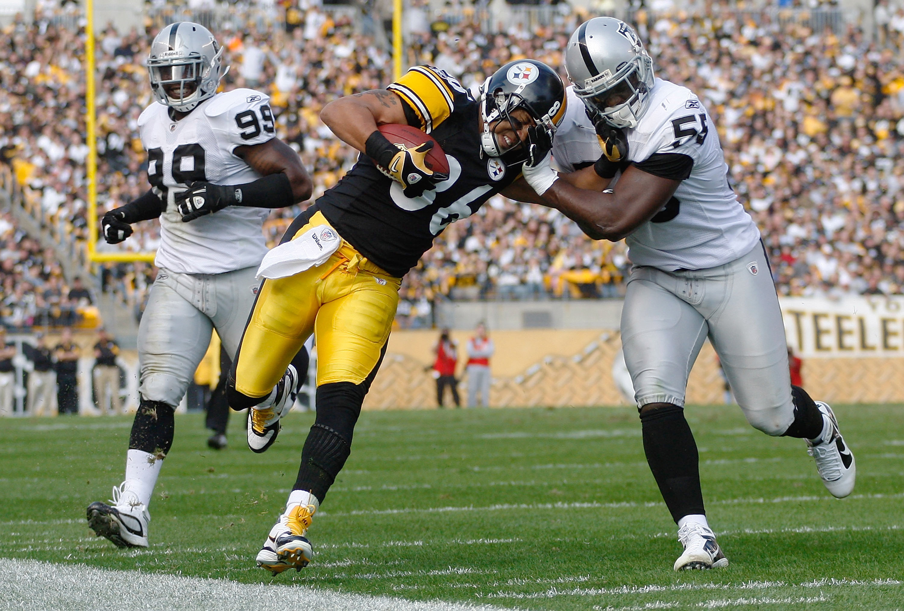 PITTSBURGH - NOVEMBER 21:  Hines Ward #86 of the Pittsburgh Steelers attempts to stiff arm Rolando McClain #55 of the Oakland Raiders after a catch during the game on November 21, 2010 at Heinz Field in Pittsburgh, Pennsylvania.  (Photo by Jared Wickerham