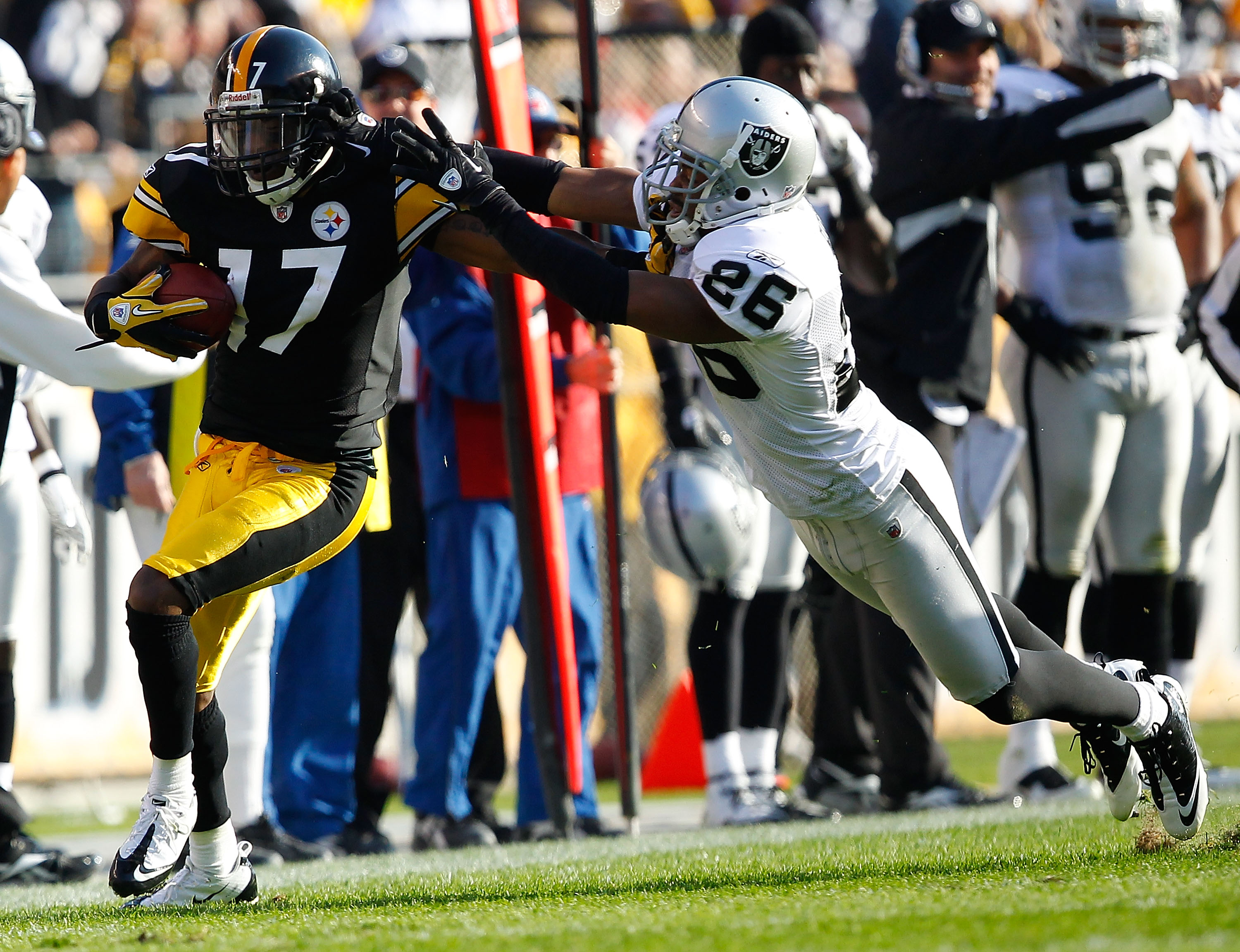 PITTSBURGH - NOVEMBER 21:  Mike Wallace #17 of the Pittsburgh Steelers attempts to outrun a tackle by Stanford Routt #26 of the Oakland Raiders during the game on November 21, 2010 at Heinz Field in Pittsburgh, Pennsylvania.  (Photo by Jared Wickerham/Get