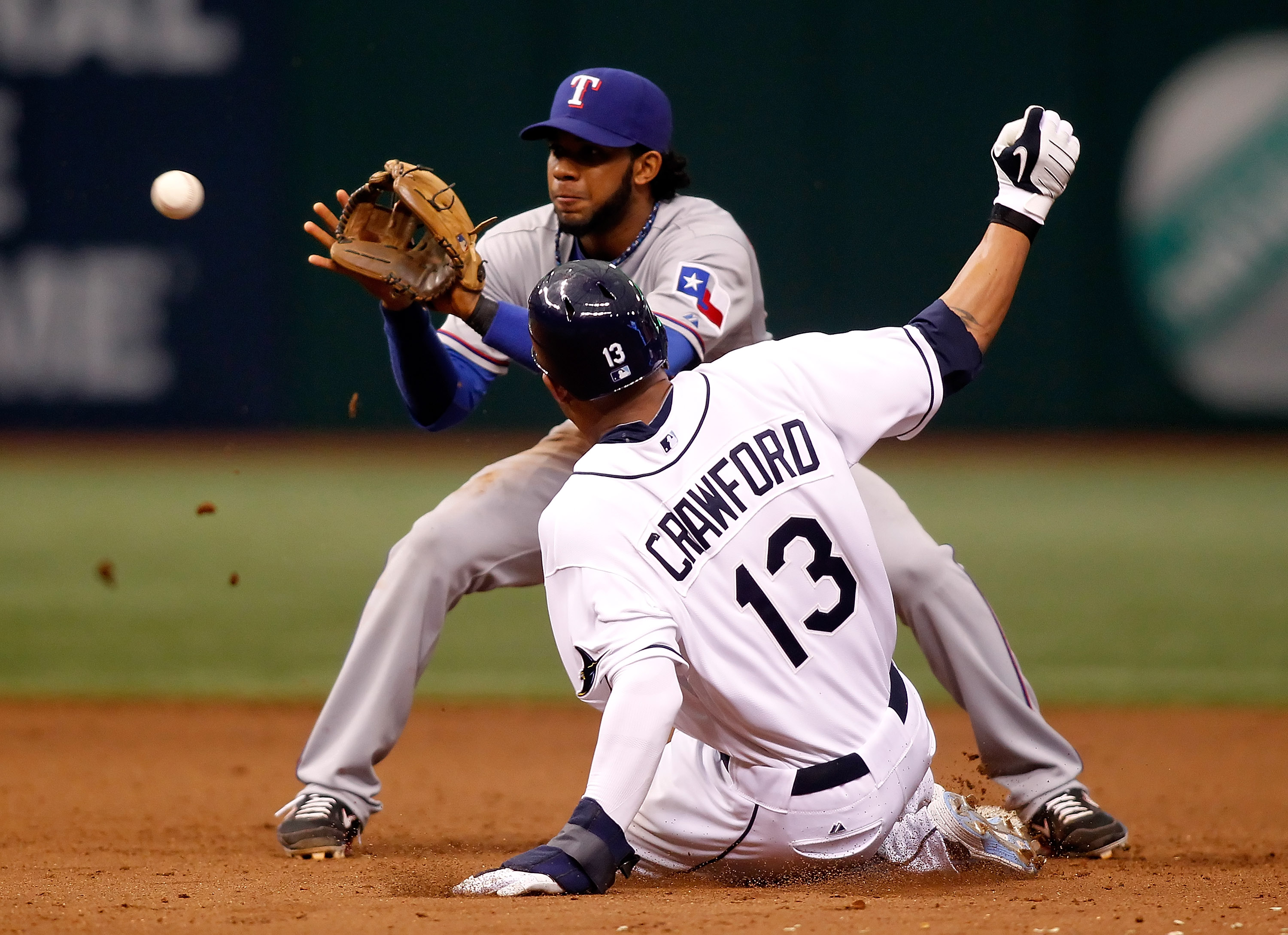 ST. PETERSBURG, FL - OCTOBER 06:  Outfielder Carl Crawford #13 of the Tampa Bay Rays steals second base as shortstop Elvis Andrus #1 of the Texas Rangers takes the throw during Game 1 of the ALDS at Tropicana Field on October 6, 2010 in St. Petersburg, Fl
