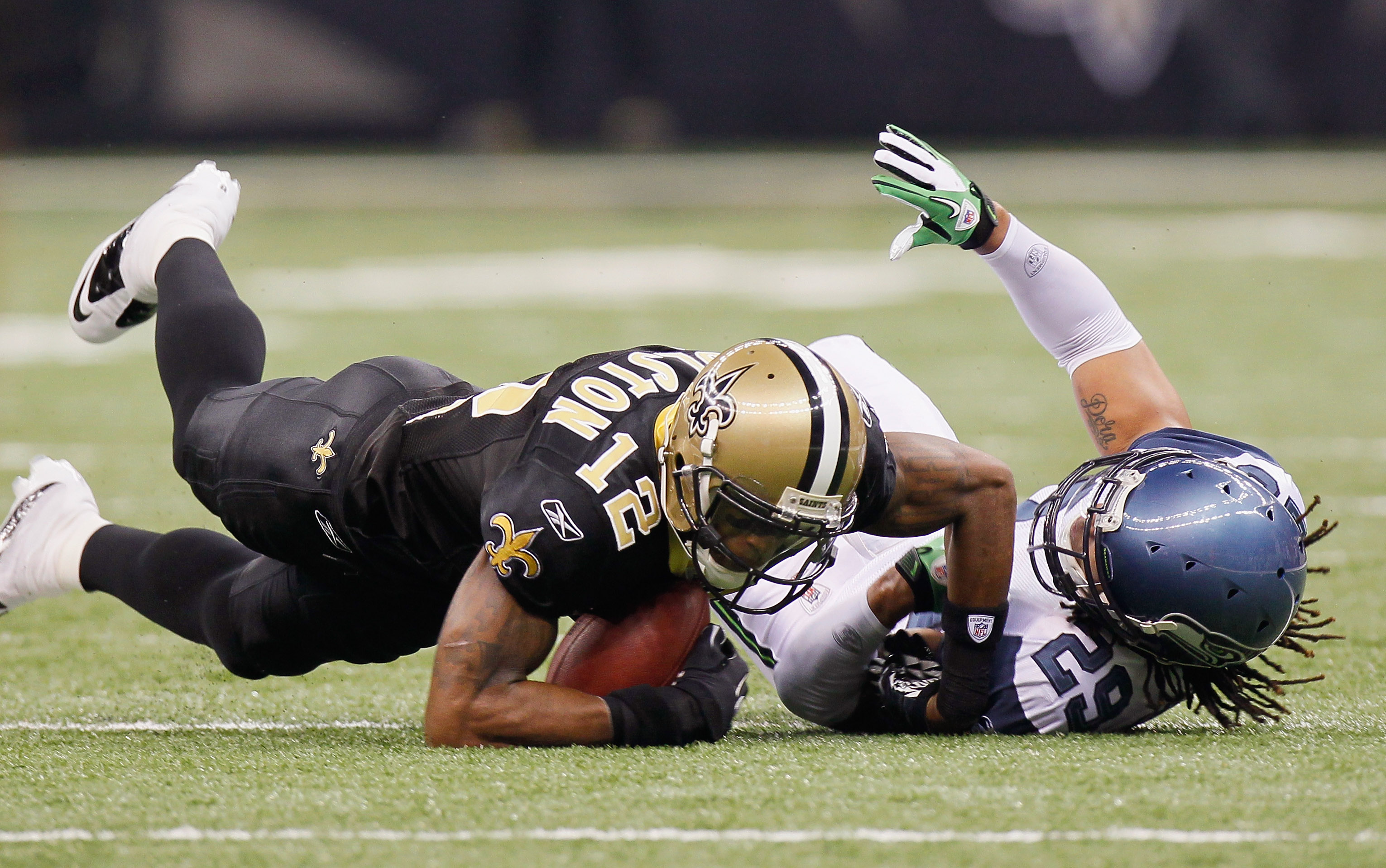 NEW ORLEANS - NOVEMBER 21:  Marques Colston #12 of the New Orleans Saints is tackled by Earl Thomas #29 of the Seattle Seahawks at Louisiana Superdome on November 21, 2010 in New Orleans, Louisiana.  (Photo by Kevin C. Cox/Getty Images)