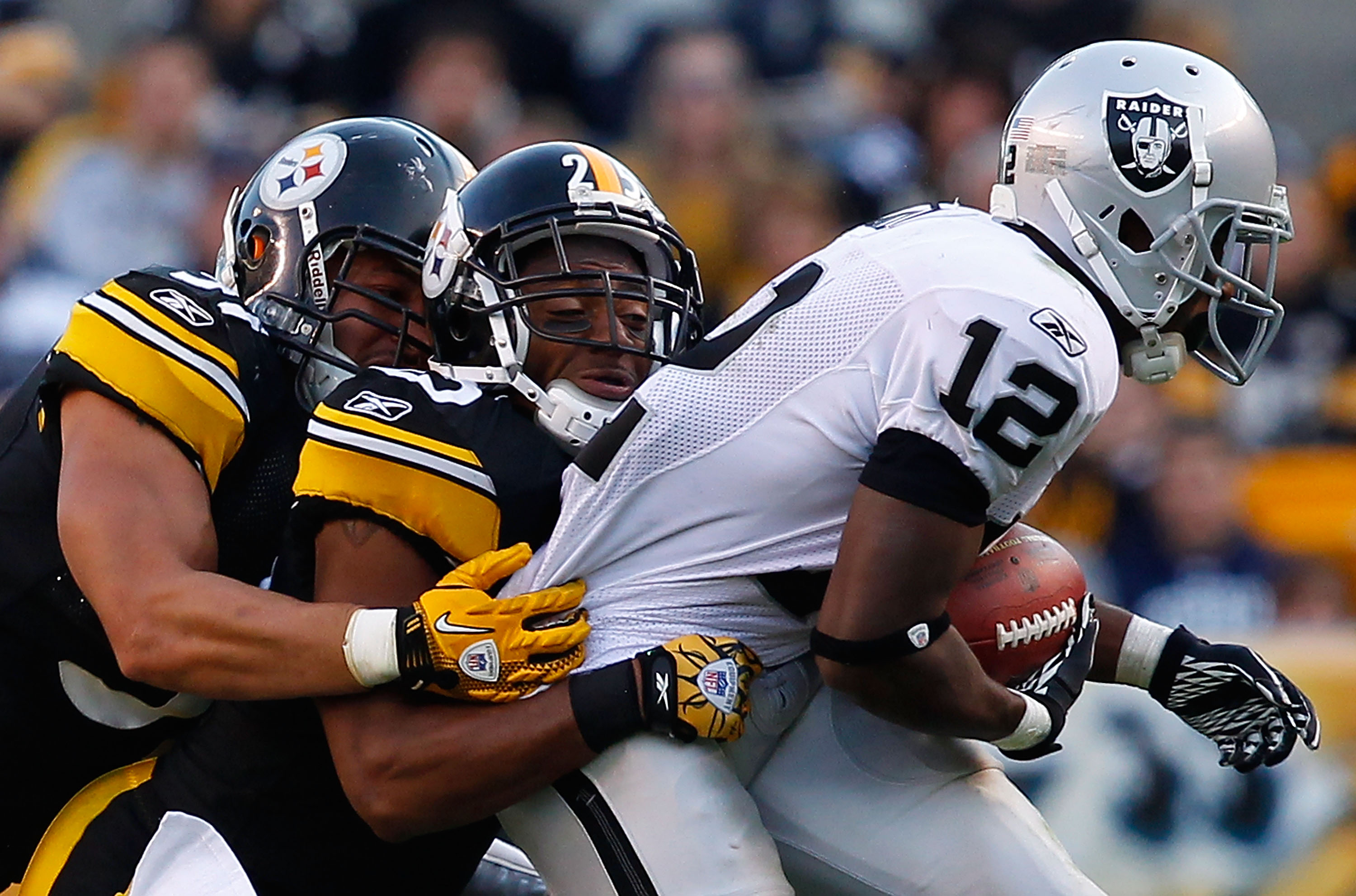 PITTSBURGH - NOVEMBER 21:  Ryan Clark #25 and James Farrior #51 of the Pittsburgh Steelers tackle Jacoby Ford #12 of the Oakland Raiders during the game on November 21, 2010 at Heinz Field in Pittsburgh, Pennsylvania.  (Photo by Jared Wickerham/Getty Imag