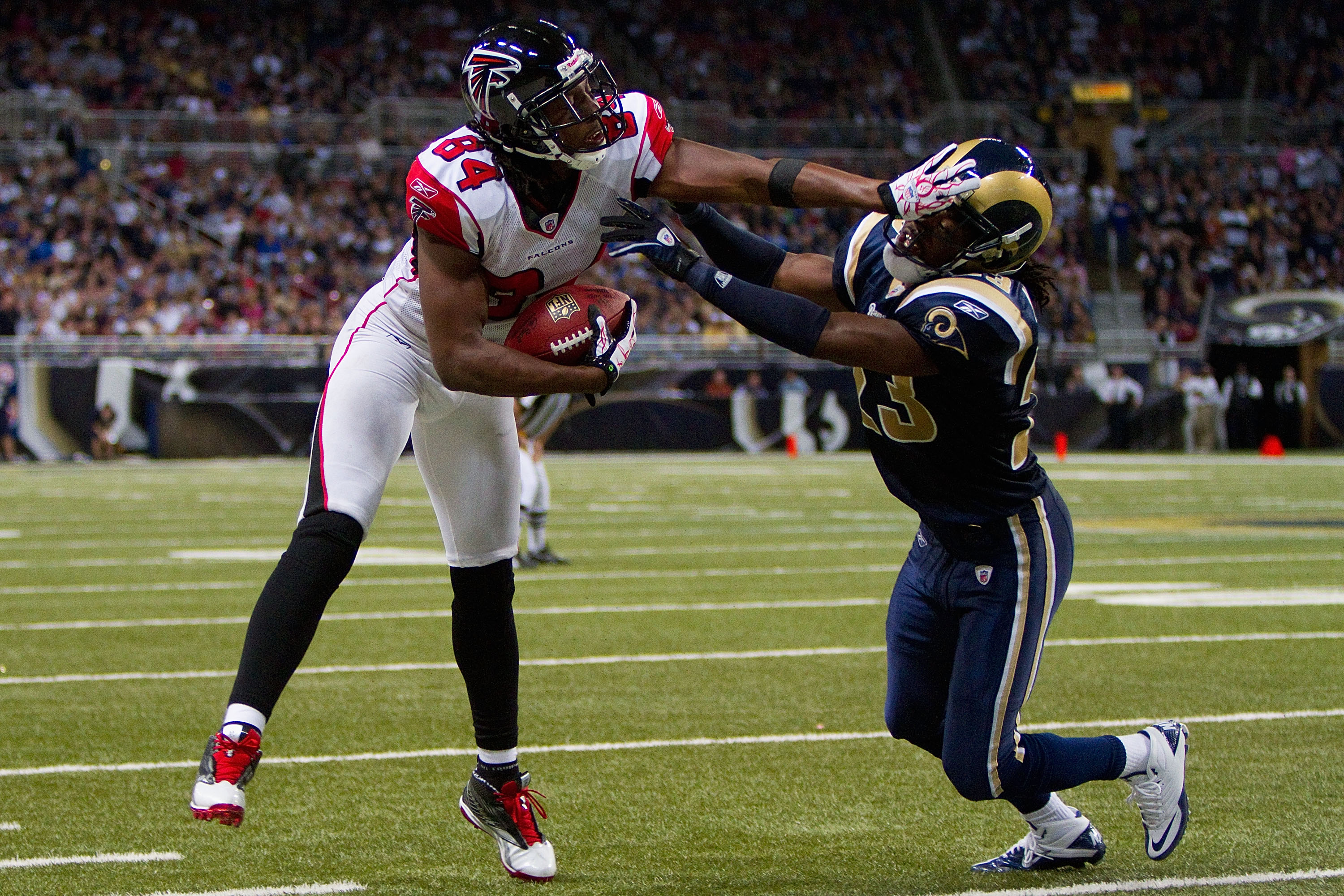 ST. LOUIS - NOVEMBER 21: Roddy White #84 of the Atlanta Falcons stiff arms Jerome Murphy #23 of the St. Louis Rams at the Edward Jones Dome on November 21, 2010 in St. Louis, Missouri.  The Falcons beat the Rams 34-17.  (Photo by Dilip Vishwanat/Getty Ima