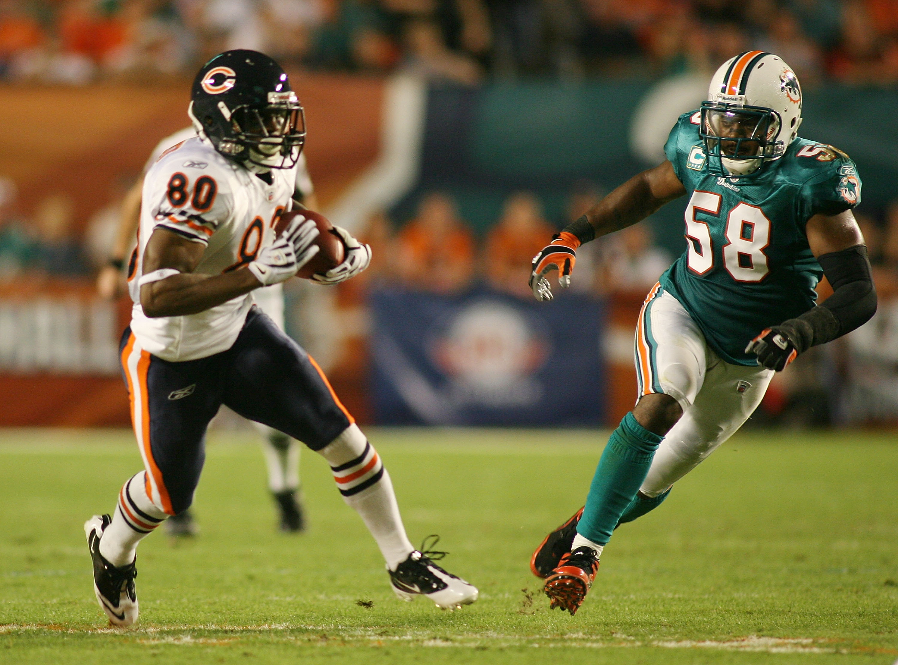 MIAMI - NOVEMBER 18:  Receiver Earl Bennett #80 of the Chicago Bears runs from linebacker Karlos Dansby #58 of the Miami Dolphins at Sun Life Stadium on November 18, 2010 in Miami, Florida.  (Photo by Marc Serota/Getty Images)
