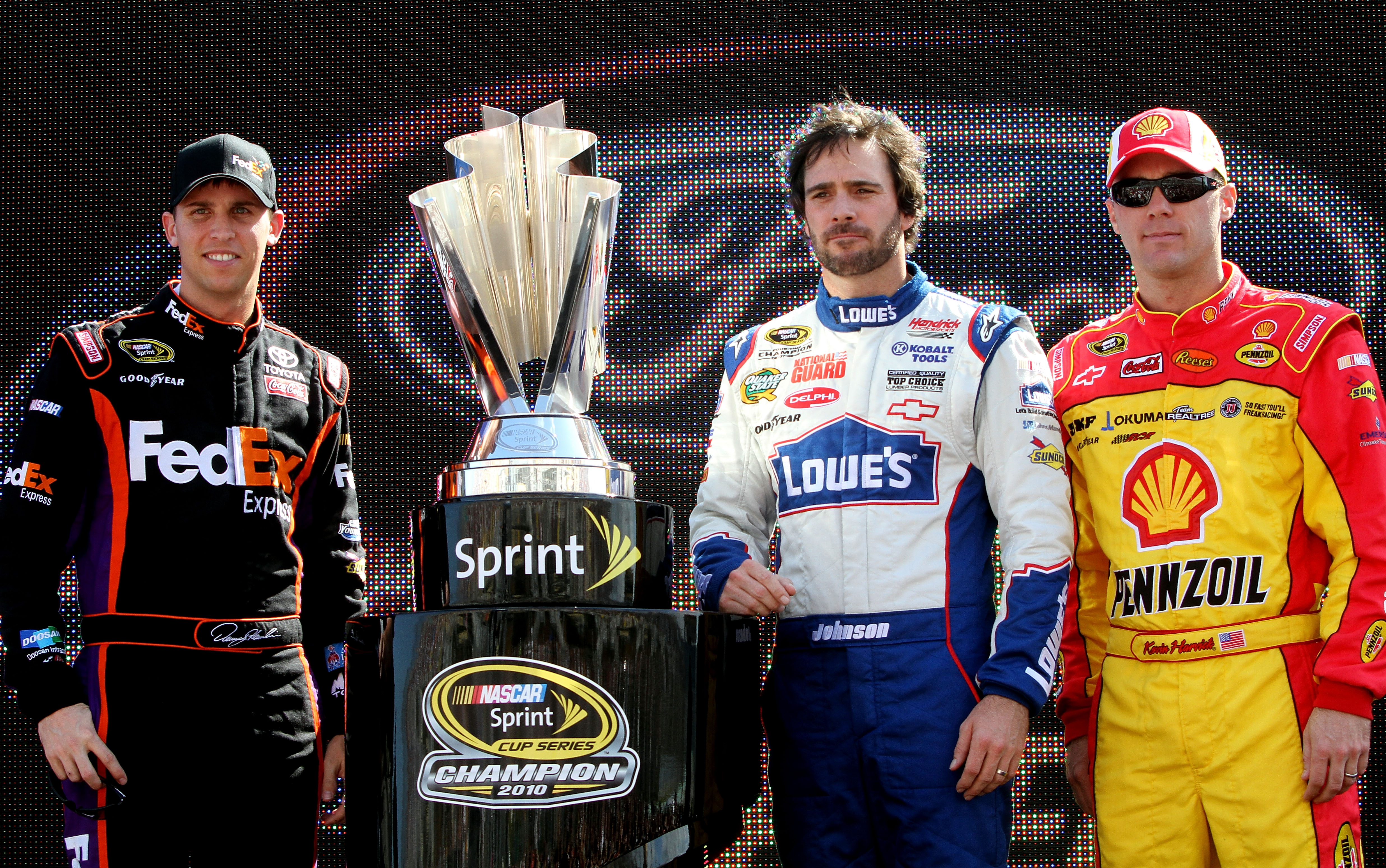 HOMESTEAD, FL - NOVEMBER 21:  (L-R) Denny Hamlin, driver of the #11 FedEx Toyota, stands next to the Sprint Cup trophy with Jimmie Johnson, driver of the #48 Lowe's Chevrolet, and Kevin Harvick, driver of the #29 Shell/Pennzoil Chevrolet, during the NASCA