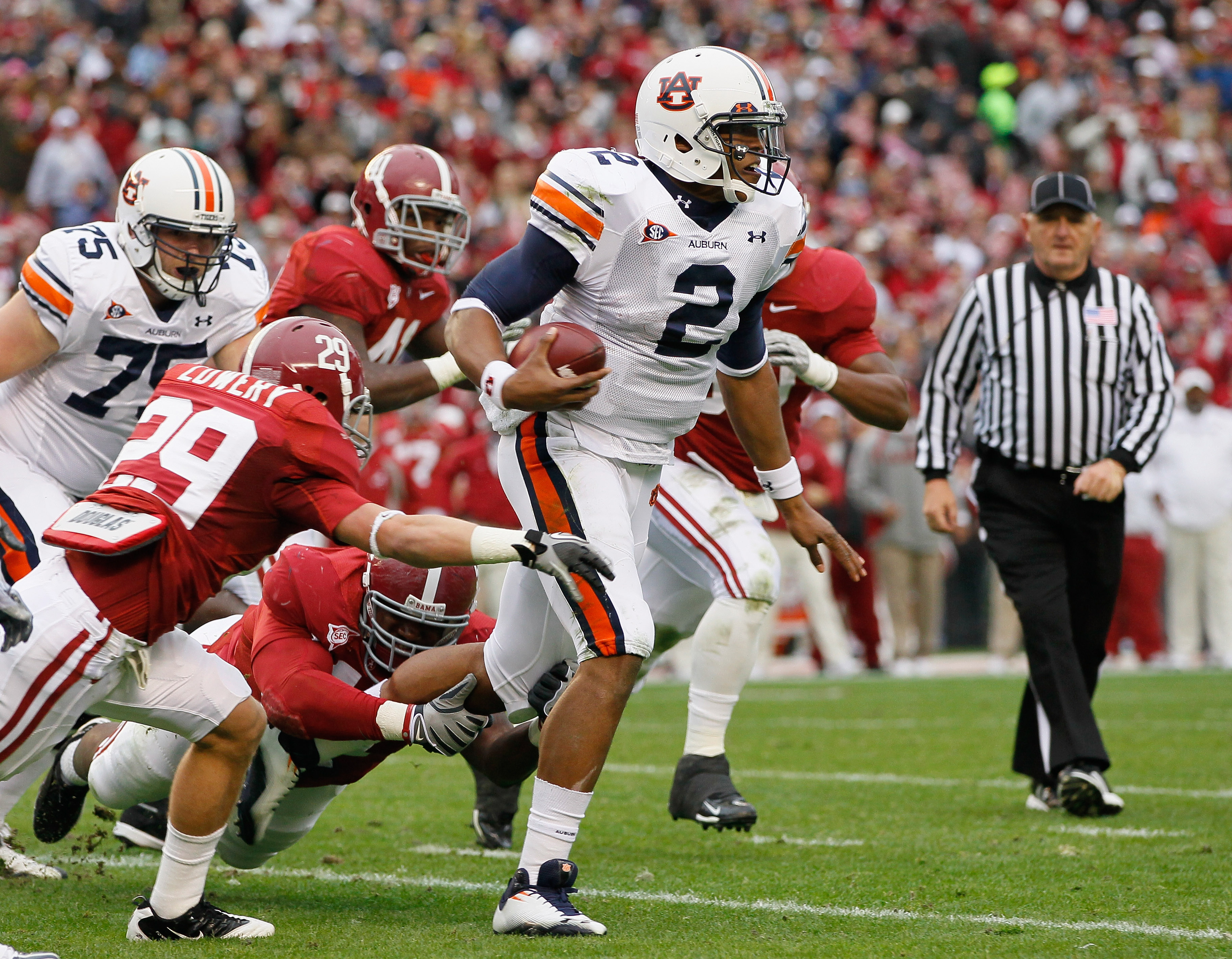 TUSCALOOSA, AL - NOVEMBER 26:  Quarterback Cam Newton #2 of the Auburn Tigers rushes upfield away from Will Lowery #29 and Marcell Dareus #57 of the Alabama Crimson Tide at Bryant-Denny Stadium on November 26, 2010 in Tuscaloosa, Alabama.  (Photo by Kevin
