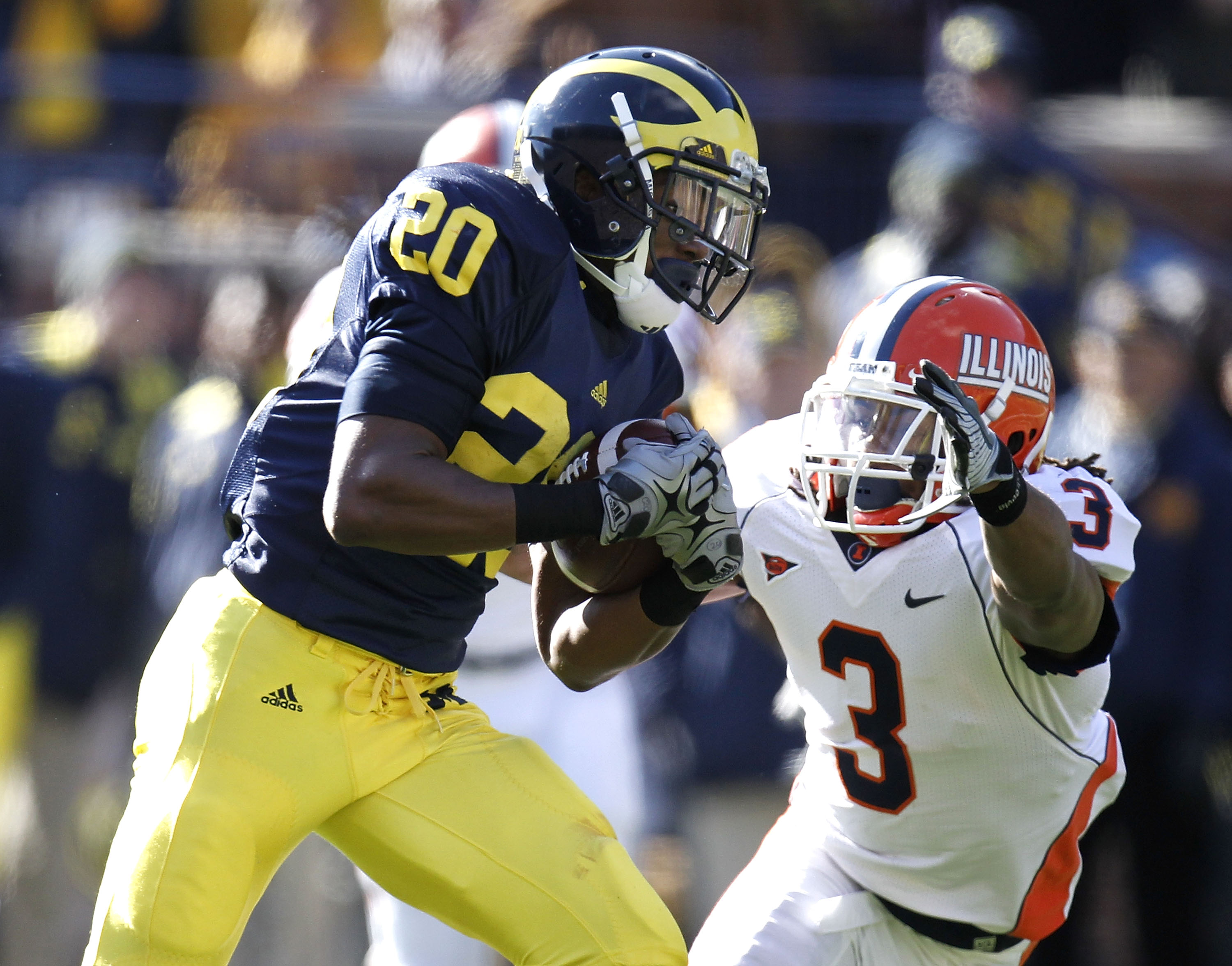 ANN ARBOR, MI - NOVEMBER 06:  Michael Shaw #20 of the Michigan Wolverines runs for a third quarter touchdown around the tackle of Tavon Wilson #3 of the Illinios Fighting Illini at Michigan Stadium on November 6, 2010 in Ann Arbor, Michigan. Michigan won