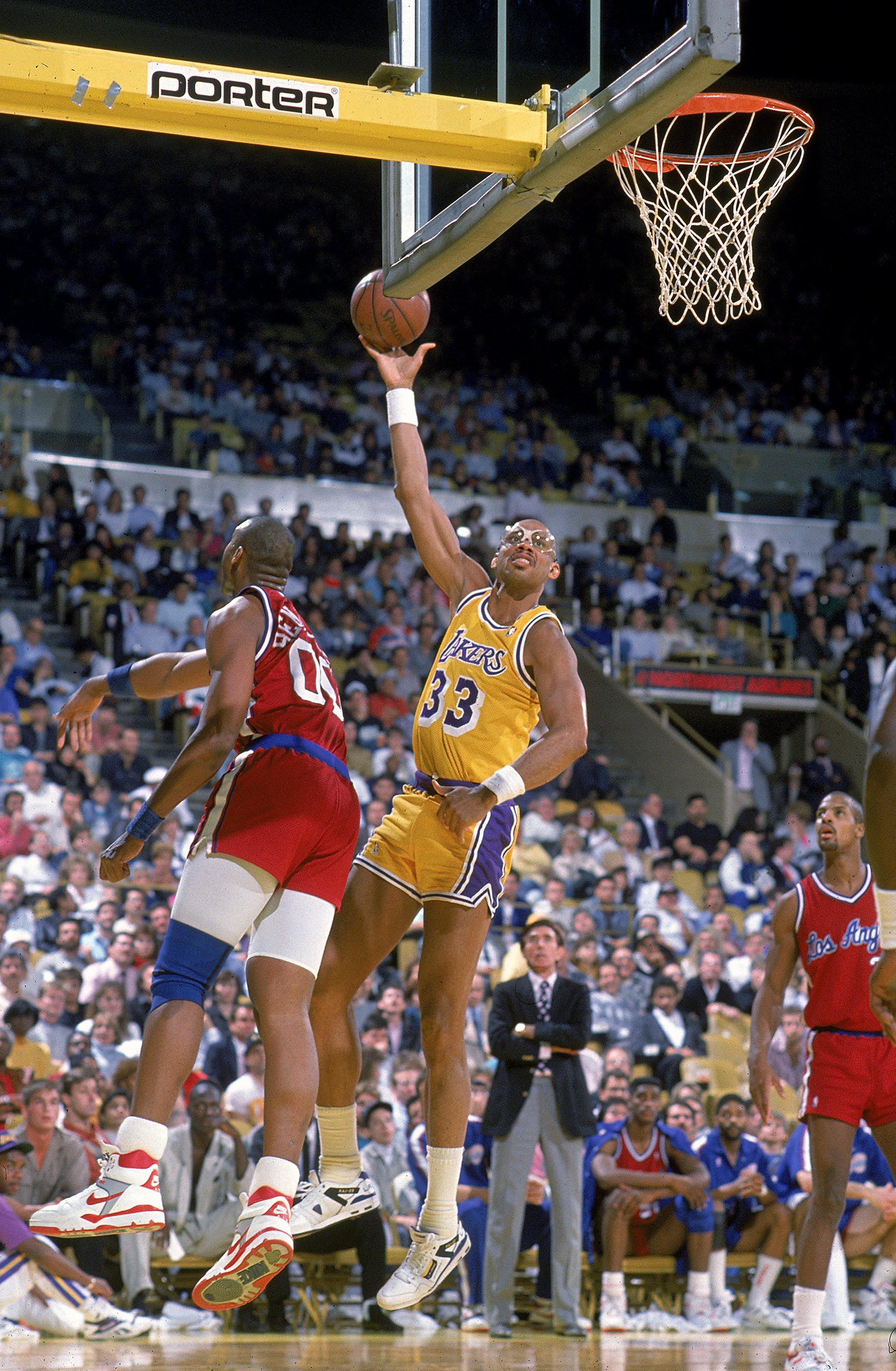 1989: Kareem Abdul- Jabbar of the Los Angeles Lakers makes a layup as Benoit Benjamin of the LA Clippers tries to block him.  Mandatory Credit: Stephen Dunn  /Allsport