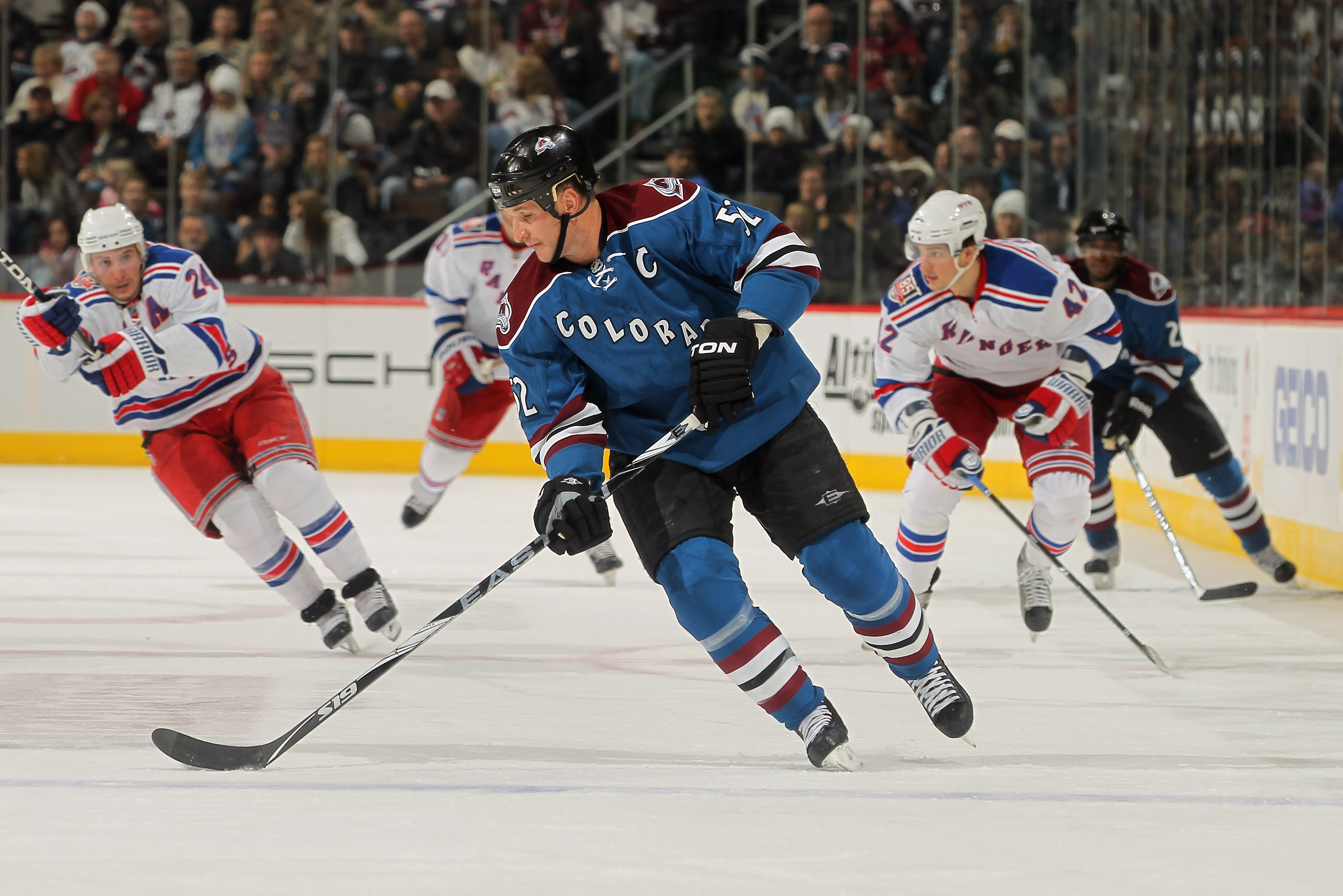 DENVER - NOVEMBER 19:  Adam Foote #52 of the Colorado Avalanche controls the puck against the New York Rangers at the Pepsi Center on November 19, 2010 in Denver, Colorado. The Avalanche defeated the Rangers 5-1.  (Photo by Doug Pensinger/Getty Images)