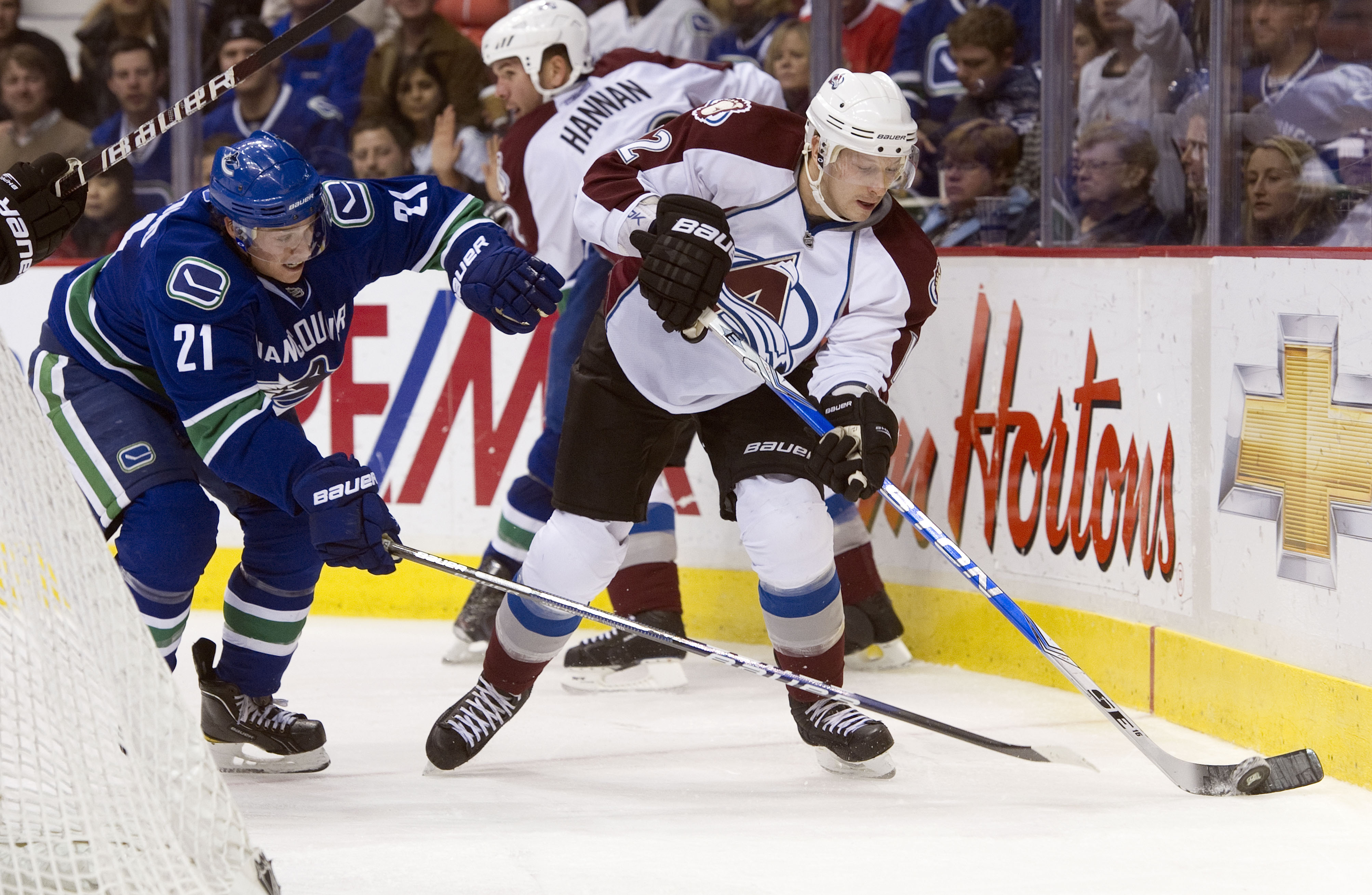 VANCOUVER, CANADA - NOVEMBER 24: Mason Raymond #21 of the Vancouver Canucks tries to check Kevin Porter #12 of the Colorado Avalanche off the puck during the second period in NHL action on November 24, 2010 at Rogers Arena in Vancouver, British Columbia,