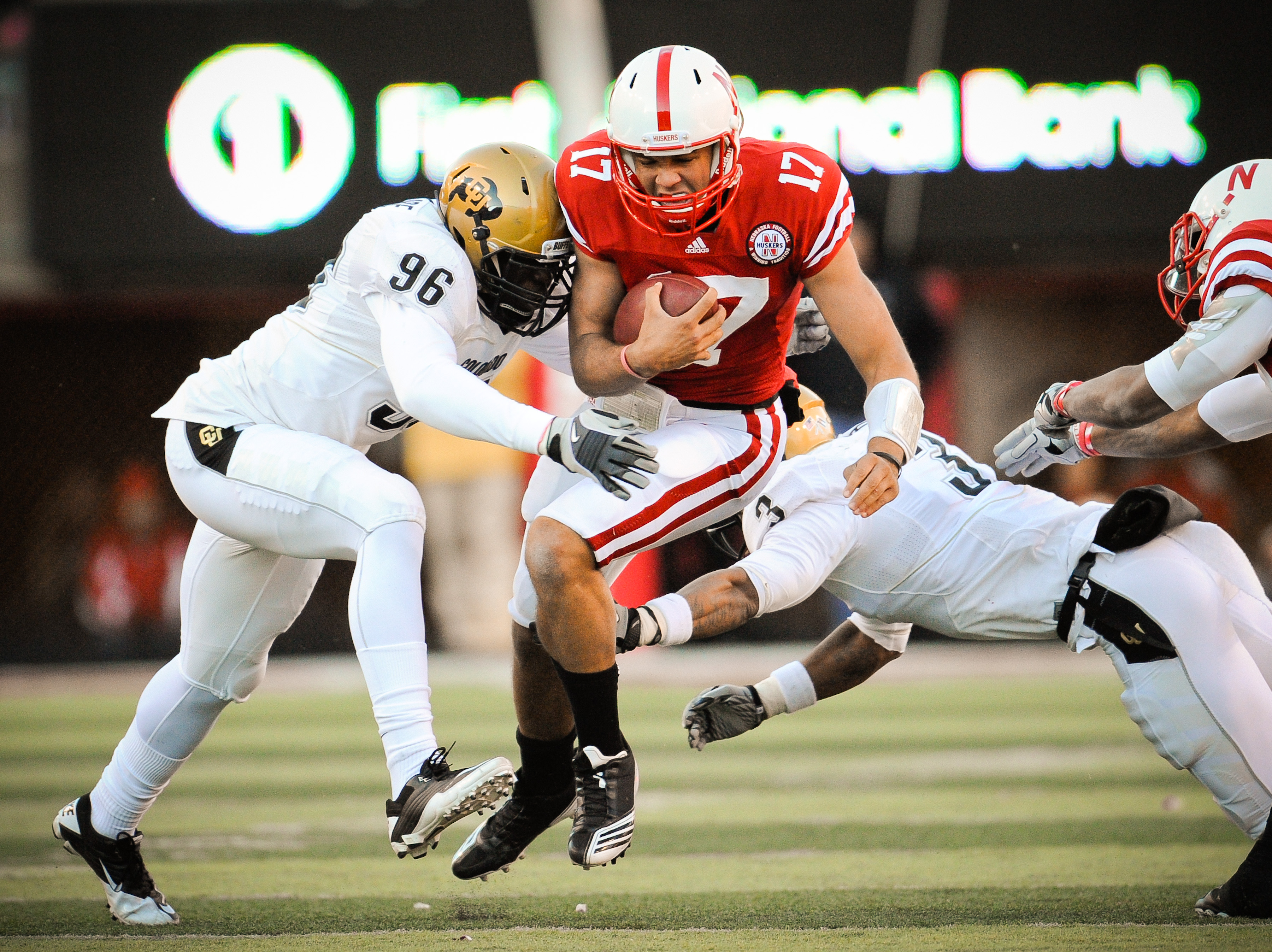 LINCOLN, NE - NOVEMBER 26: Cody Green #17 of the Nebraska Cornhuskers takes a hit from Chidera Uzo-Diribe #96 and Jimmy Smith #3 of the Colorado Buffaloes during the first half of their game at Memorial Stadium on November 26, 2010 in Lincoln, Nebraska.