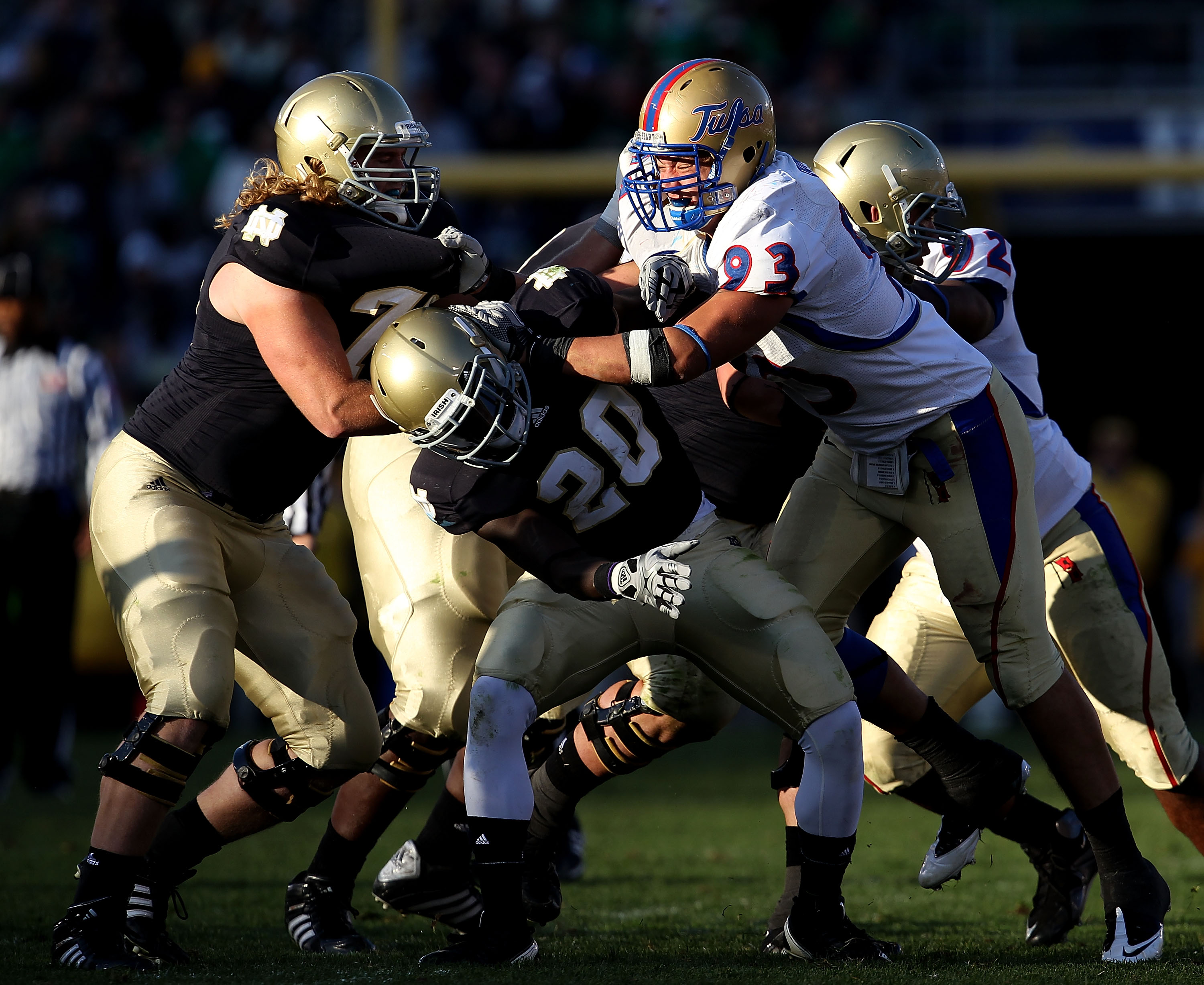 SOUTH BEND, IN - OCTOBER 30: Cory Dorris #93 of the Tulsa Golden Hurricane takes on Taylor Dever #75 and Cierre Wood #20 of the Notre Dame Fighting Irish at Notre Dame Stadium on October 30, 2010 in South Bend, Indiana. Tulsa defeated Notre Dame 28-27. (P