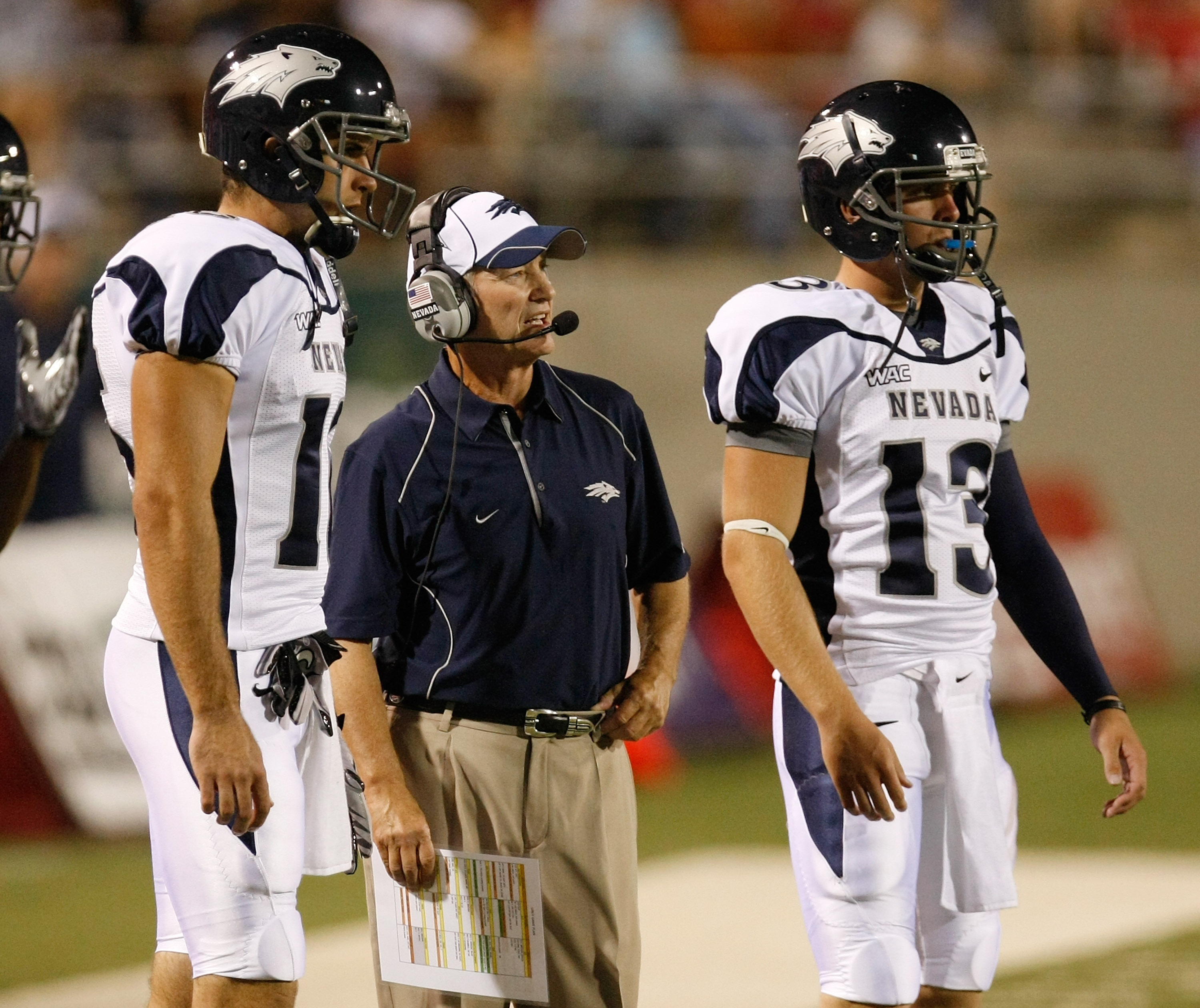 LAS VEGAS - OCTOBER 02:  Nevada Reno Wolf Pack head coach Chris Ault (C) is flanked by quarterbacks Tyler Lantrip #16 and Mason Magleby #13 as Ault watches his players take on the UNLV Rebels at Sam Boyd Stadium October 2, 2010 in Las Vegas, Nevada. Nevad