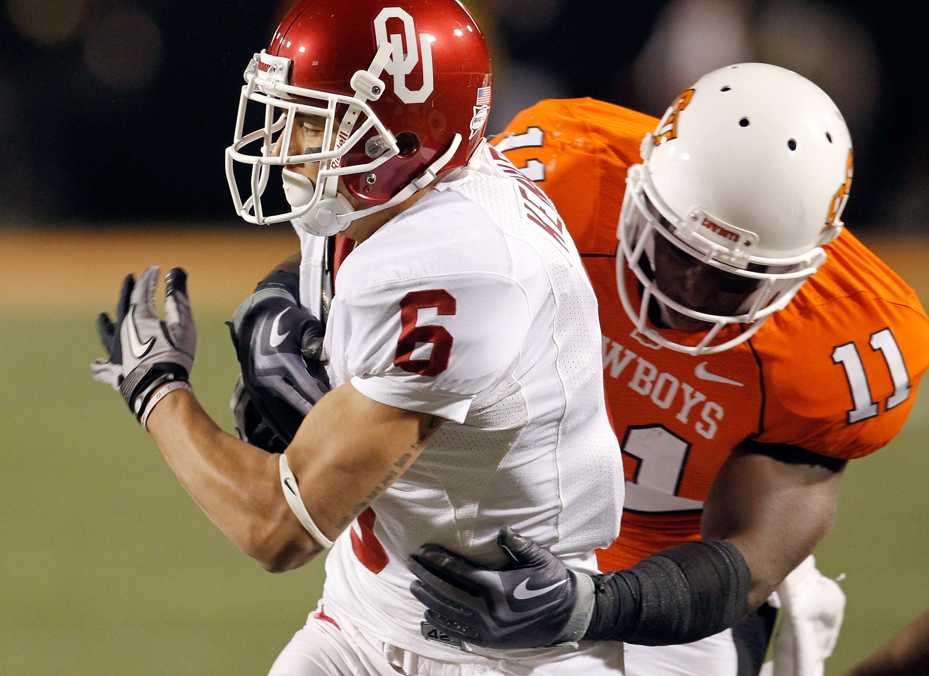 STILLWATER, OK - NOVEMBER 27:  Wide receiver Cameron Kenney #6 of the Oklahoma Sooners carries the ball against linebacker Shaun Lewis #11 of the Oklahoma State Cowboys at Boone Pickens Stadium on November 27, 2010 in Stillwater, Oklahoma.  The Sooners be