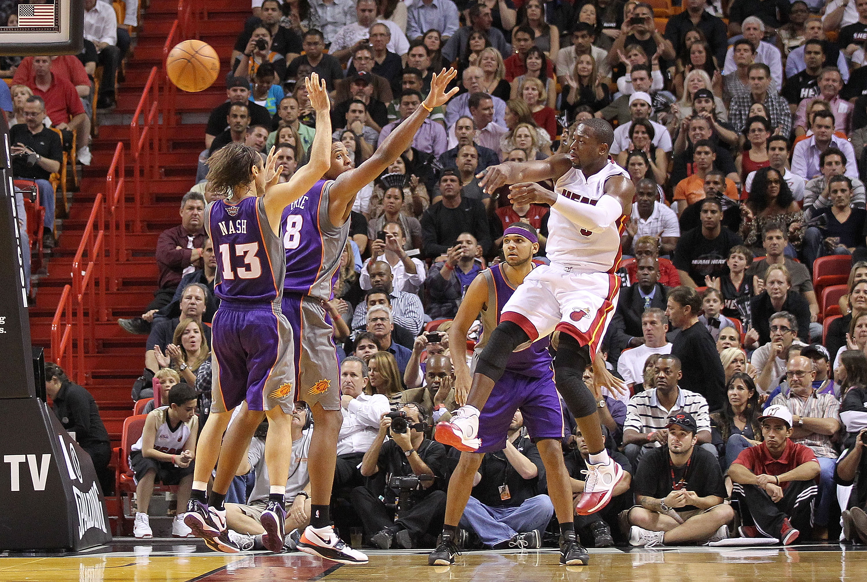 MIAMI - NOVEMBER 17:  Dwyane Wade #3 of the Miami Heat passes the ball over Steve Nash #13 during a game against the Phoenix Suns at American Airlines Arena on November 17, 2010 in Miami, Florida. NOTE TO USER: User expressly acknowledges and agrees that,