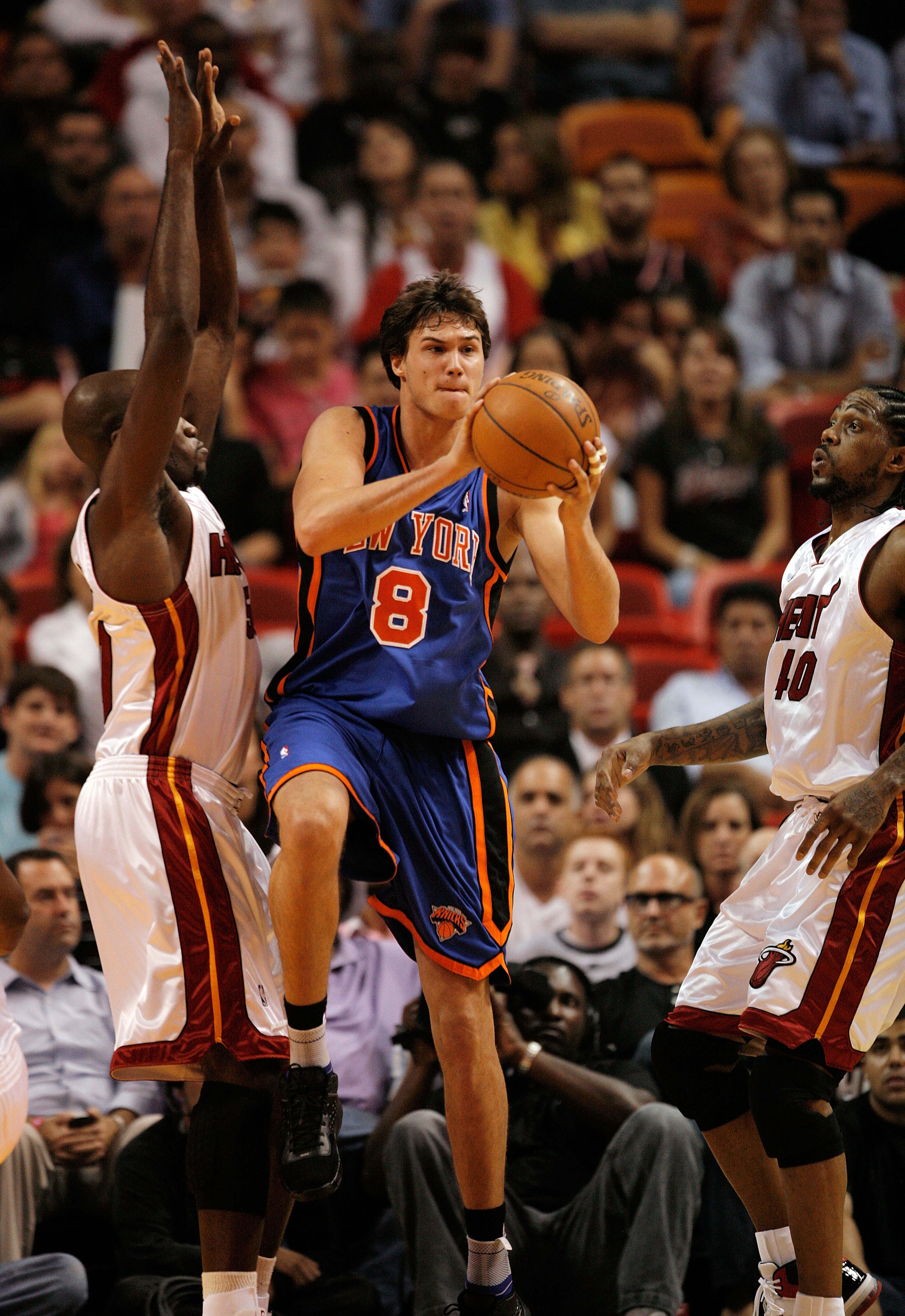 MIAMI - OCTOBER 28:  Danilo Gallinari #8 of the New York Knicks passes away from the pressure of Joel Anthony #50 and Udonis Haslem #40 of the Miami Heat at AmericanAirlines Arena on October 28, 2009 in Miami, Florida. The Heat defeated the Knicks 115-93.