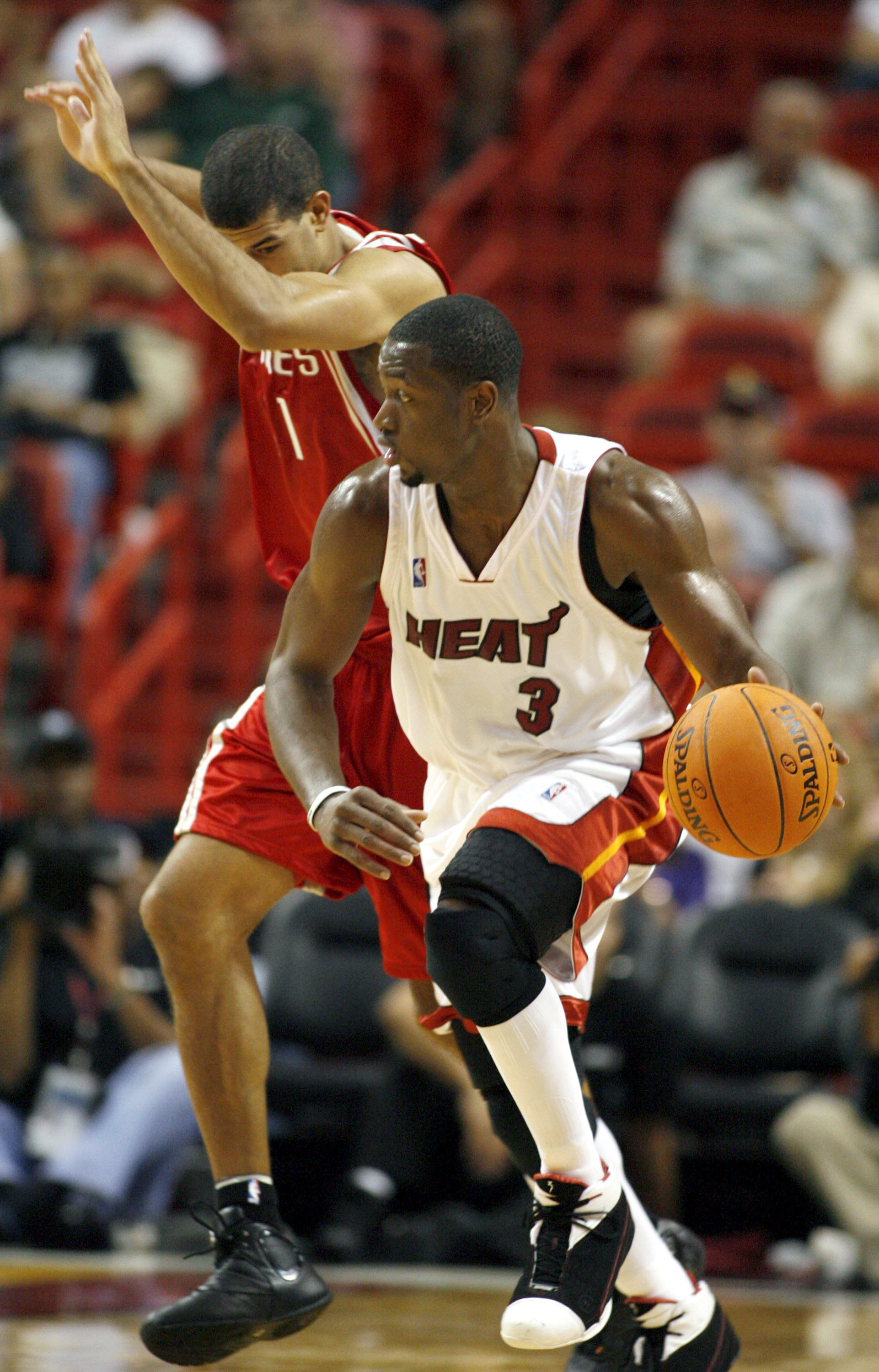 MIAMI - OCTOBER 25:  Guard Dwyane Wade #3 of the Miami Heat drives away from Shane Battier #31of the Houston Rockets during their preseason game on October 25, 2006 at the American Airlines Arena in Miami  Florida.  NOTE TO USER: User expressly acknowledg