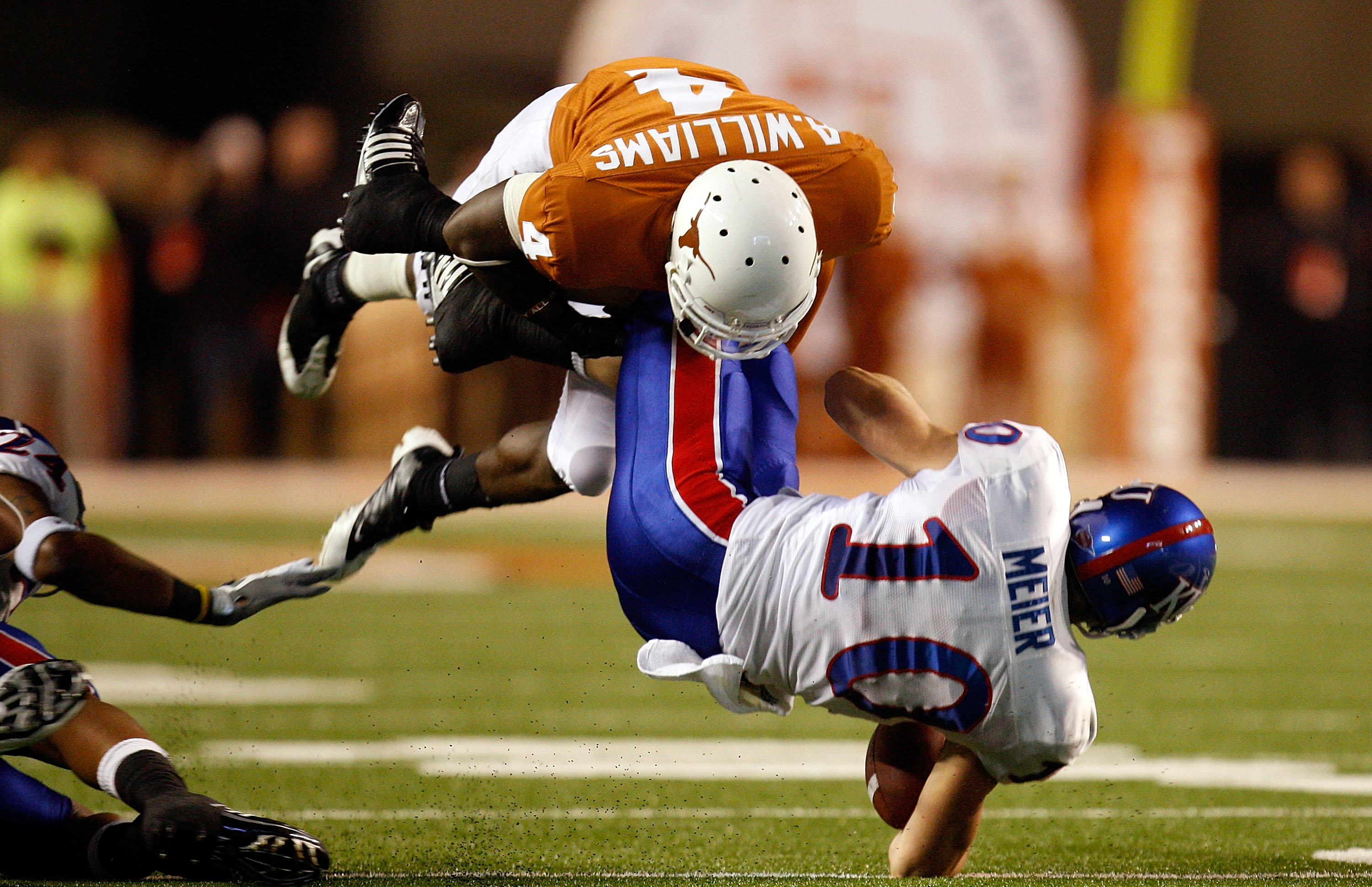 AUSTIN, TX - NOVEMBER 21:  Wide receiver Kerry Meier #10 of the Kansas Jayhawks is tackled by Aaron Williams #4 of the Texas Longhorns at Darrell K Royal-Texas Memorial Stadium on November 21, 2009 in Austin, Texas.  (Photo by Ronald Martinez/Getty Images