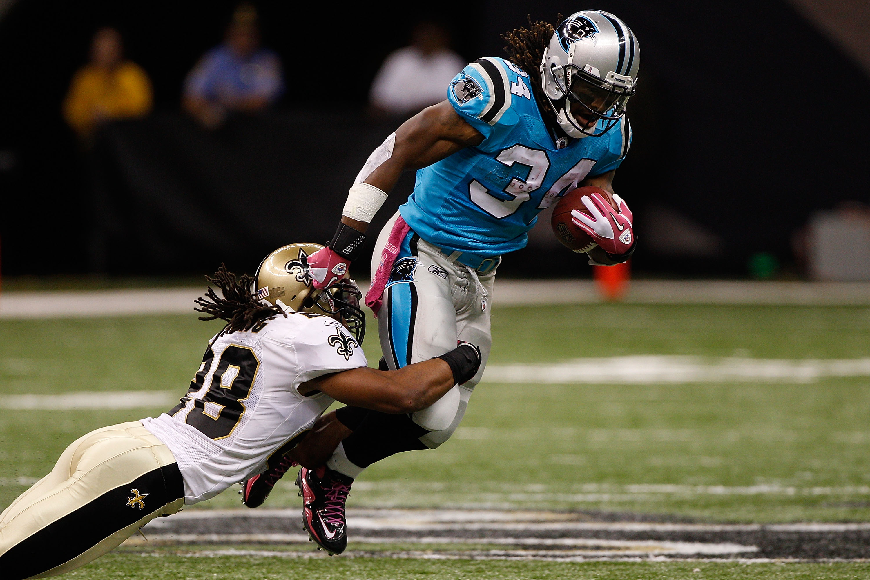NEW ORLEANS - OCTOBER 03:  Usama Young #28 of the New Orleans Saints tackles DeAngelo Williams #34 of the Carolina Panthers at the Louisiana Superdome on October 3, 2010 in New Orleans, Louisiana.  (Photo by Chris Graythen/Getty Images)