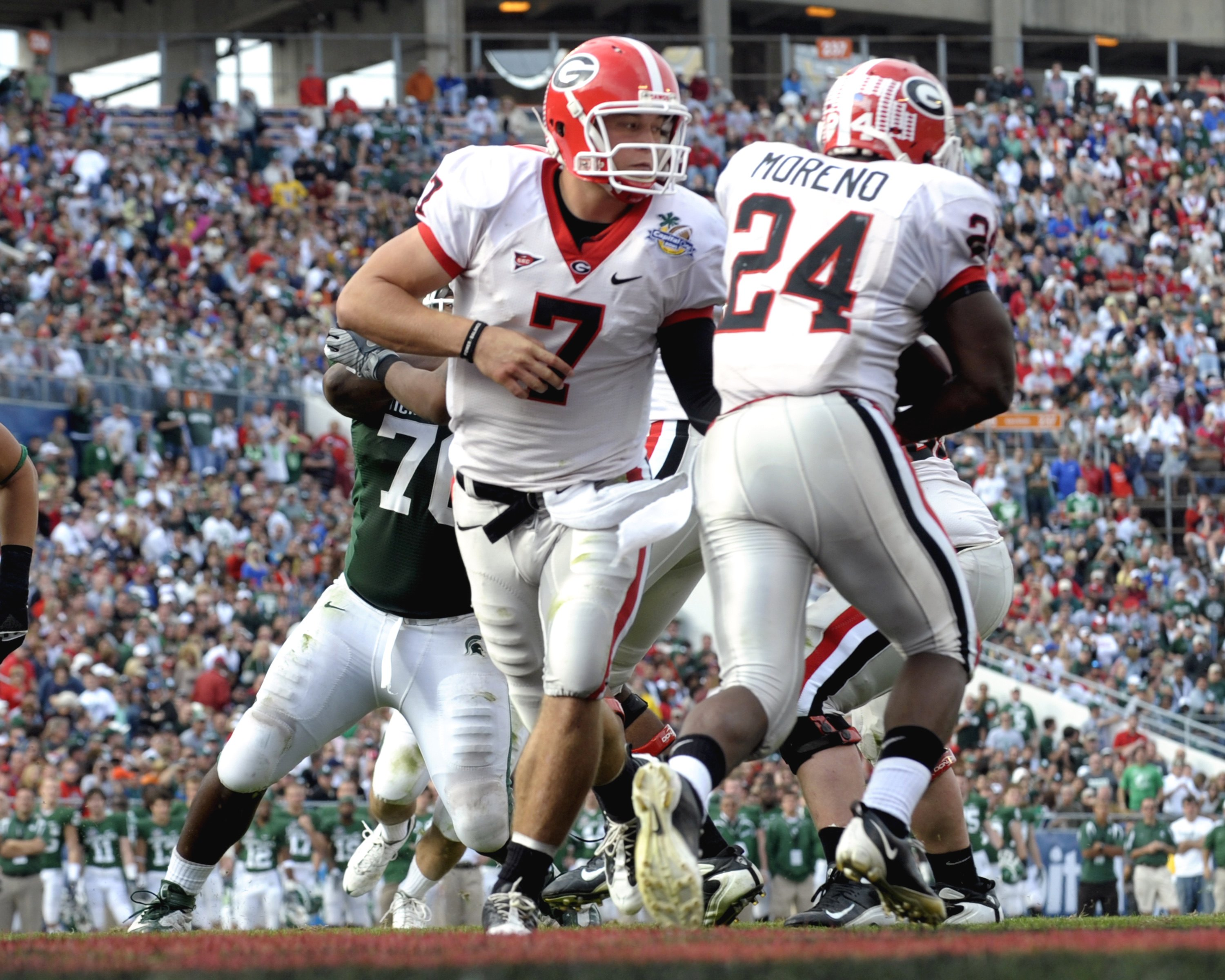 ORLANDO, FL - JANUARY 1: Running back Knowshon Moreno #24 of the University of Georgia takes a handoff from quarterback Matthew Stafford #7 against the Michigan State Spartans at the 2009 Capital One Bowl at the Citrus Bowl on January 1, 2009 in Orlando,