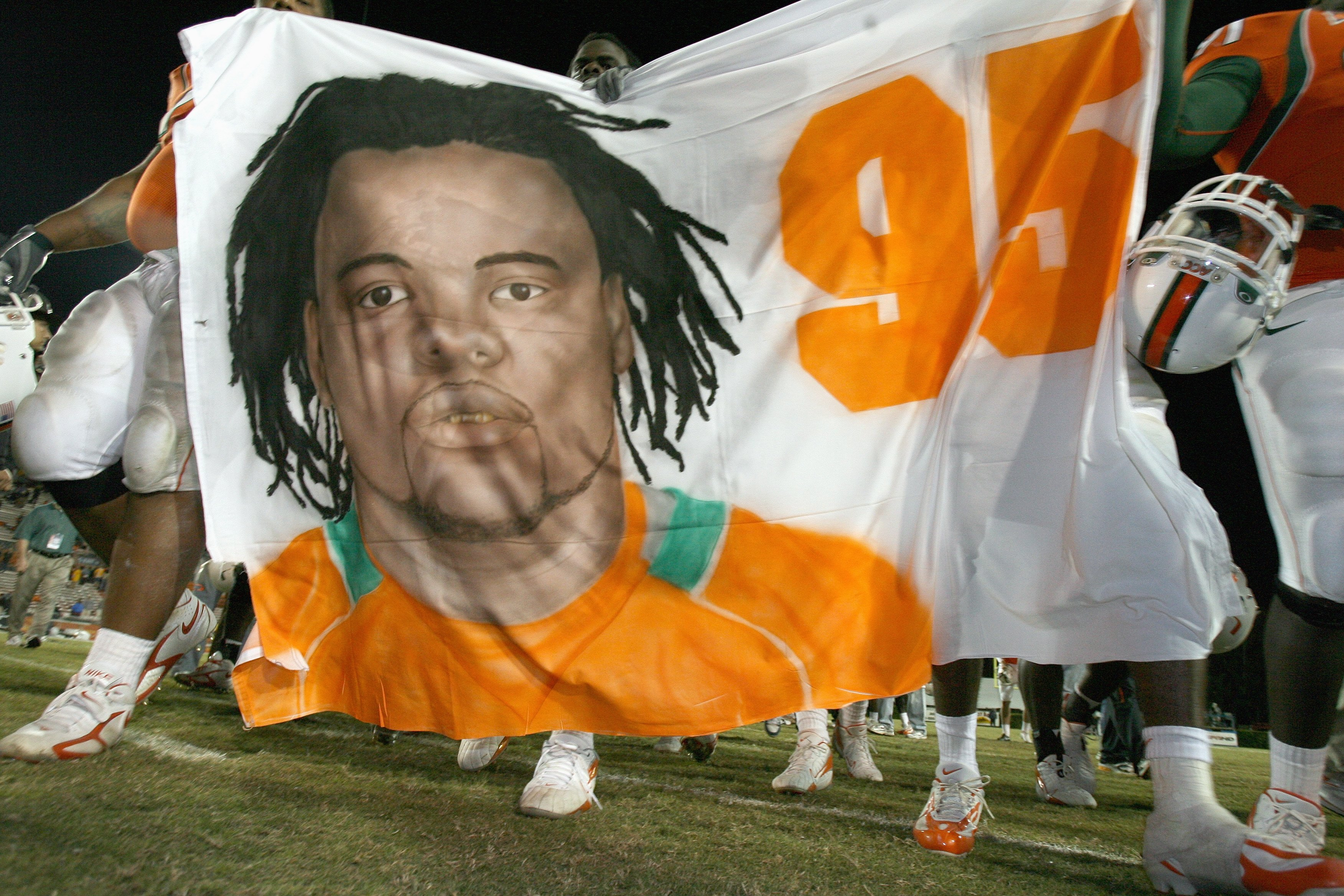 MIAMI - NOVEMBER 23: Teammates of Bryan Pata #95 of the University of Miami Hurricanes walks to mid-field after defeating the Boston College Golden Eagles at the Orange Bowl Stadium on November 23, 2006 in Miami, Florida. Pata was shot and killed after pr