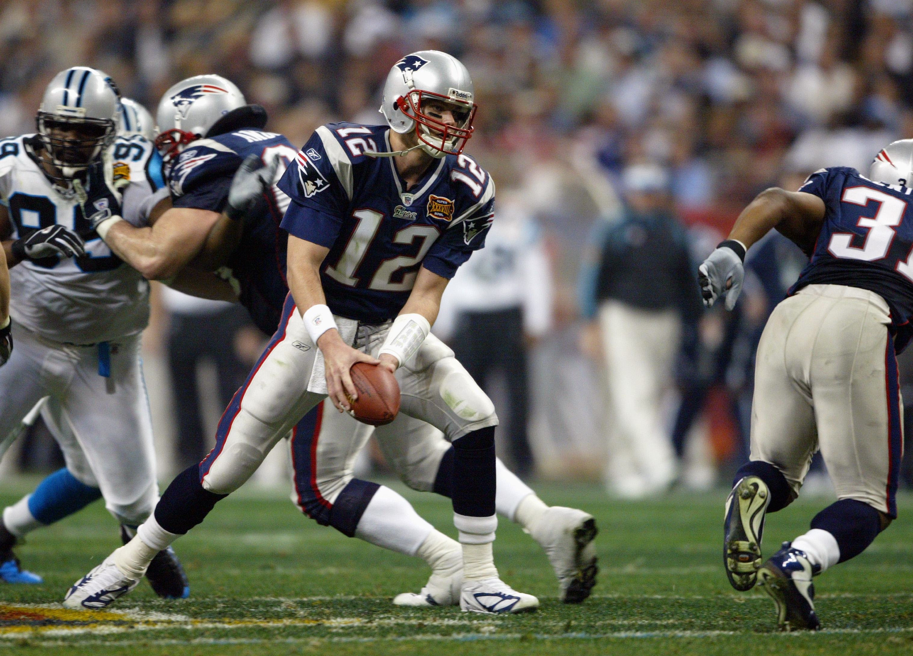 HOUSTON - FEBRUARY 1:  Quarterback Tom Brady #12 of the New England Patriots looks to toss the ball to a running back against the Carolina Panthers during Super Bowl XXXVIII at Reliant Stadium on February 1, 2004 in Houston, Texas.  The Patriots defeated
