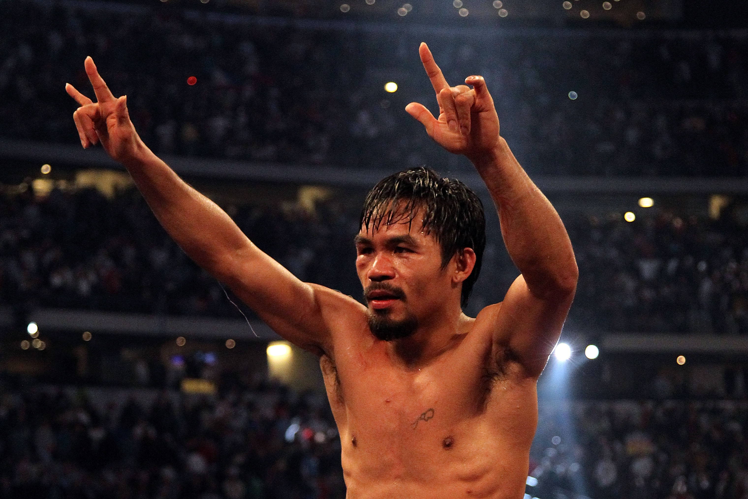 ARLINGTON, TX - MARCH 13:  Manny Pacquiao of the Philippines celebrates in the ring after defeating Joshua Clottey of Ghana during the WBO welterweight title fight at Cowboys Stadium on March 13, 2010 in Arlington, Texas. Pacquiao defeated Clottey by unan