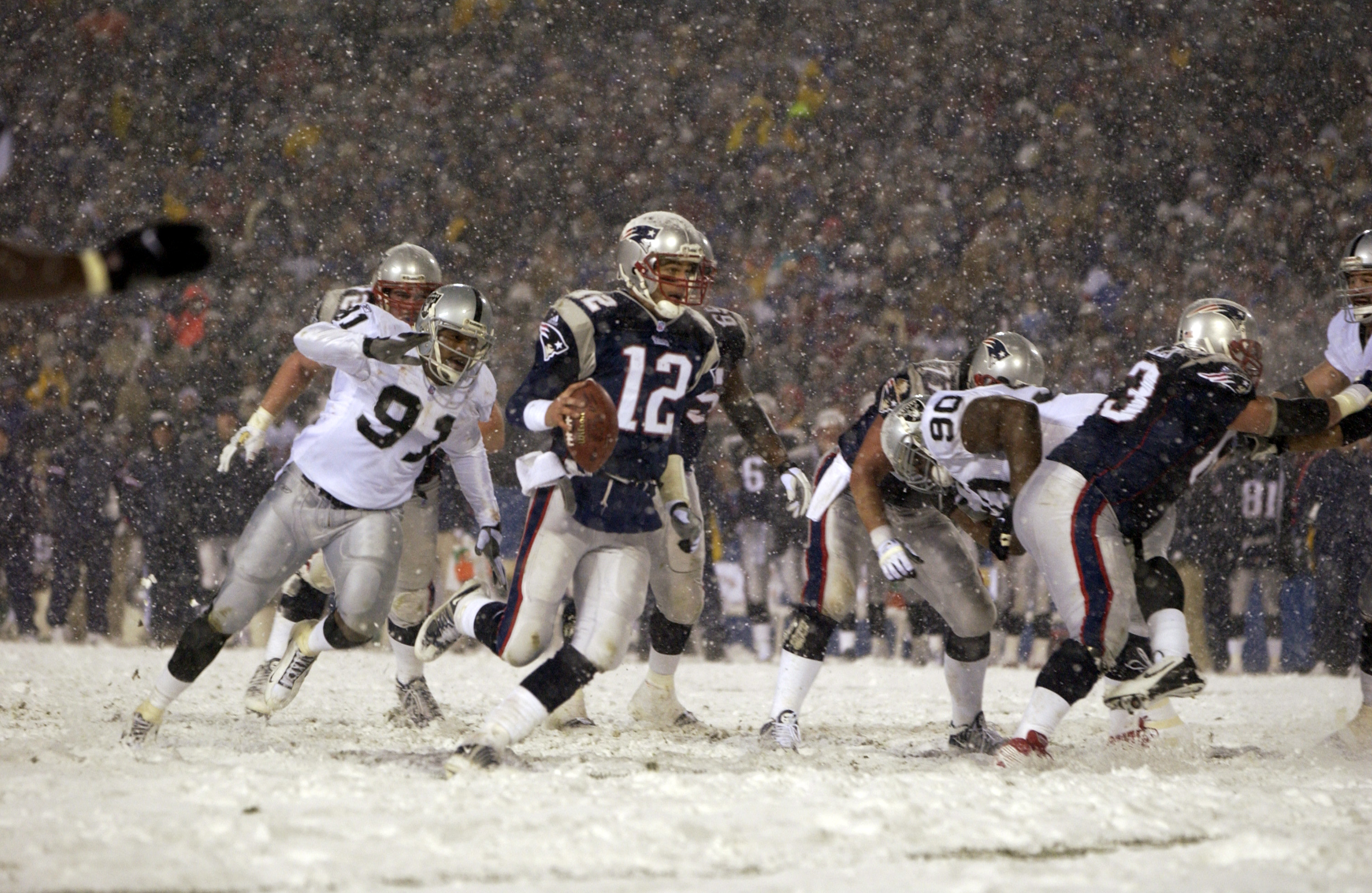 19 Jan 2002:  Quarterback  Tom Brady #12 of the New England Patriots runs in for a touchdown over the defense of Regan Upshaw #91of the Oakland Raiders during the AFC playoff game at Foxboro Stadium in Foxboro, Massachuesetts. The Patriots came from behin