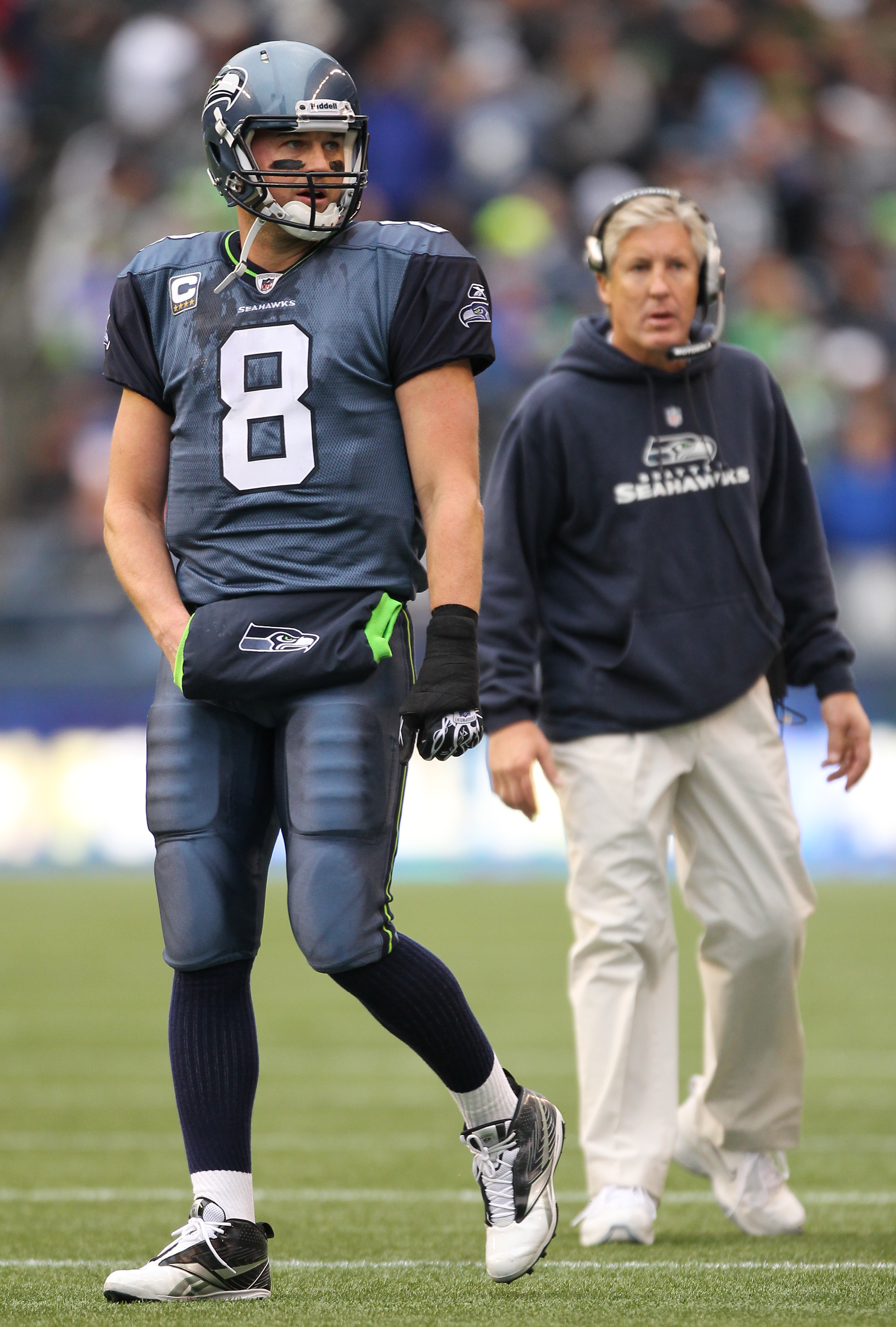 SEATTLE - DECEMBER 05:  Quarterback Matt Hasselbeck #8 of the Seattle Seahawks heads back to the huddle as head coach Pete Carroll looks on during a timeout in the game against the Carolina Panthers at Qwest Field on December 5, 2010 in Seattle, Washingto