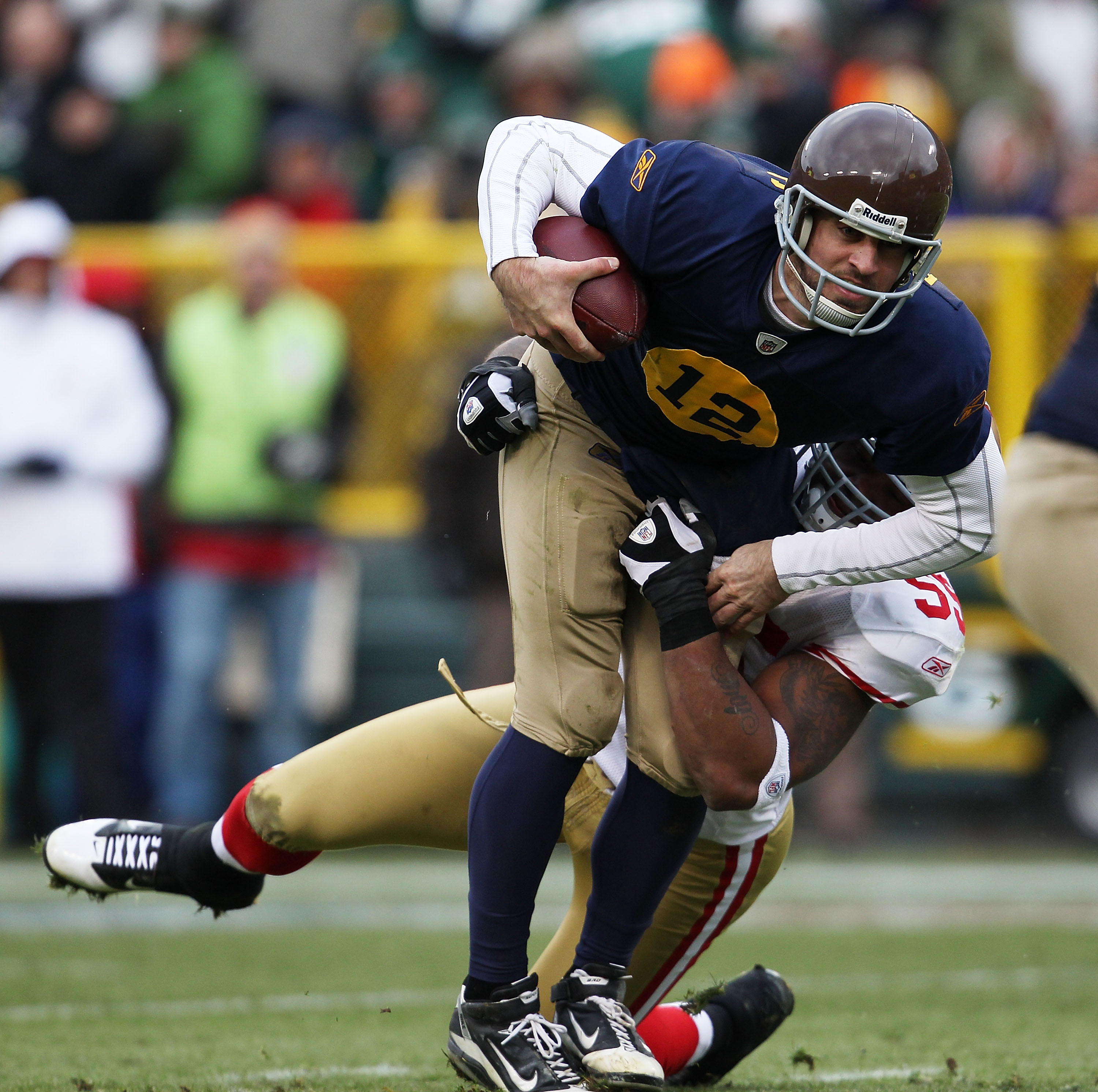 GREEN BAY, WI - DECEMBER 05: Aaron Rodgers #12 of the Green Bay Packers is sacked by Ahmad Brooks #55 of the San Francisco 49ers at Lambeau Field on December 5, 2010 in Green Bay, Wisconsin. The Packers defeated the 49ers 34-16. (Photo by Jonathan Daniel/