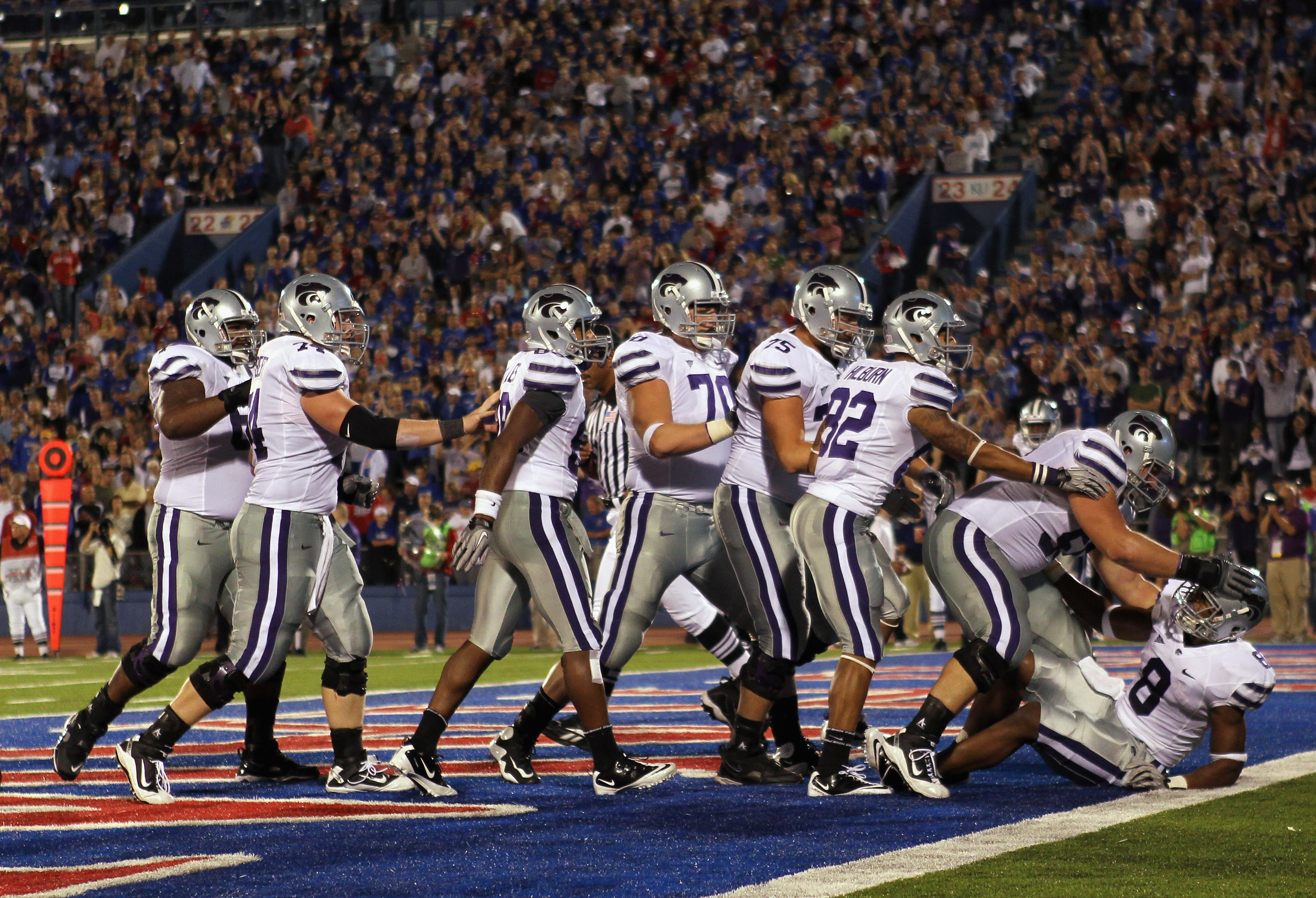 LAWRENCE, KS - OCTOBER 14:  Daniel Thomas #8 of the Kansas State Wildcats is congratulated by teammates after scoring a touchdown during the game against the Kansas Jayhawks on October 14, 2010 at Memorial Stadium in Lawrence, Kansas.  (Photo by Jamie Squ