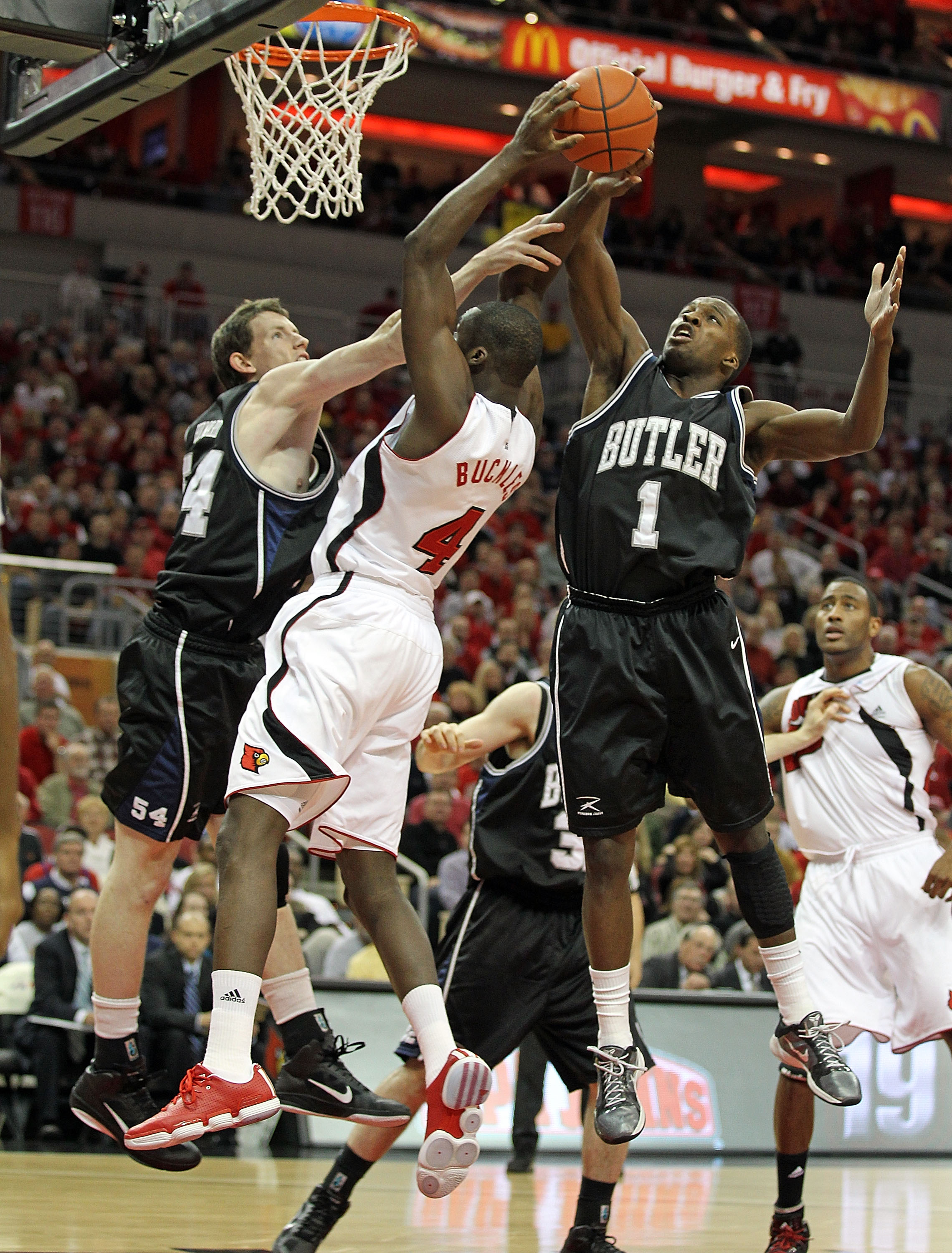 LOUISVILLE, KY - NOVEMBER 16:  Matt Howard #54 and Shelvin Mack #1 of the Butler Bulldogs defend the shot of  Rakeem Buckles #4 of the Louisville Cardinals during the game at the KFC Yum! Center on November 16, 2010 in Louisville, Kentucky.  (Photo by And