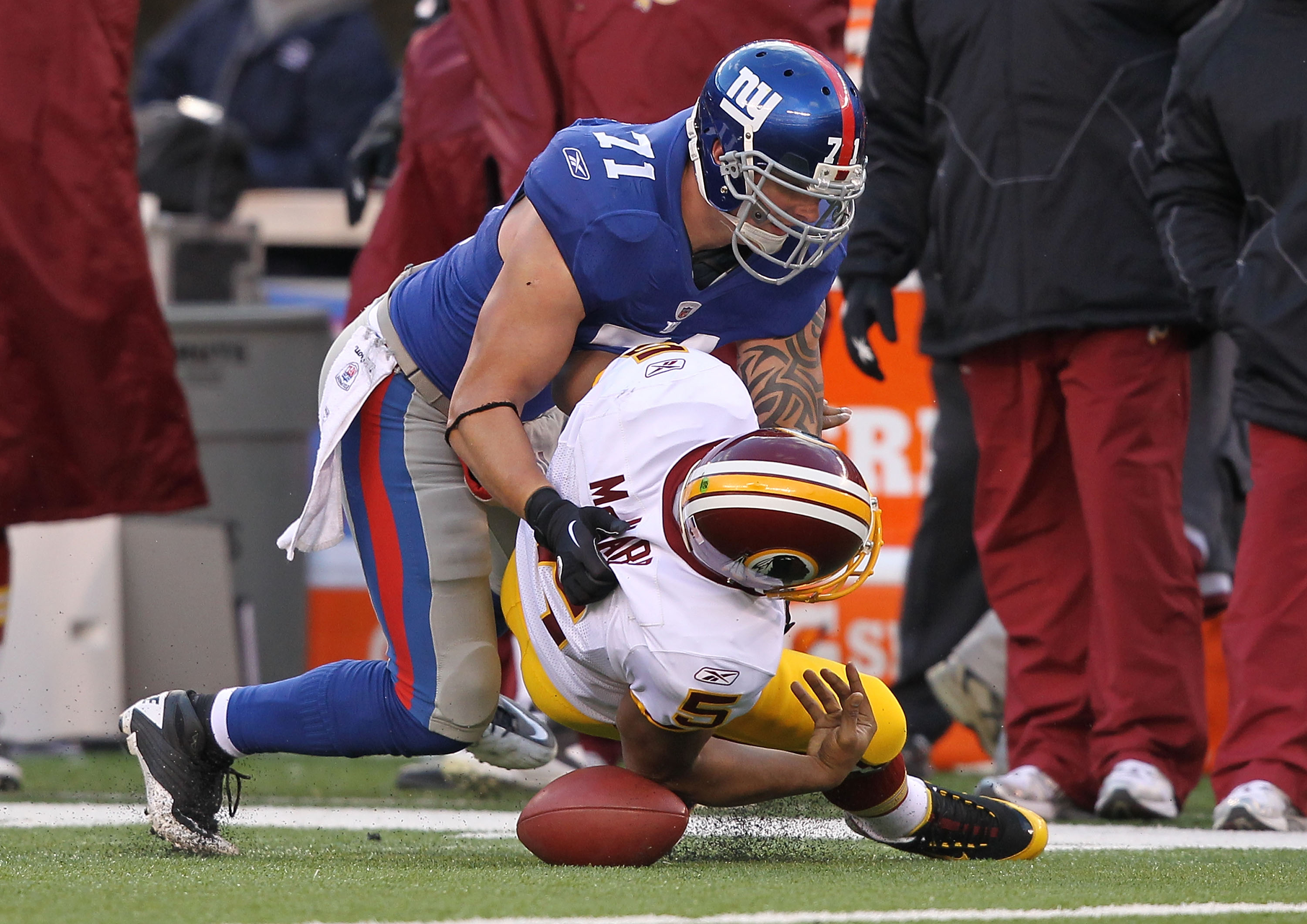 EAST RUTHERFORD, NJ - DECEMBER 05:  Dave Tollefson #71 of the New York Giants sacks Donovan McNabb #5 of the Washington Redskins who fumbles and the ball is recovered by Corey Webster #23 during their game on December 5, 2010 at The New Meadowlands Stadiu