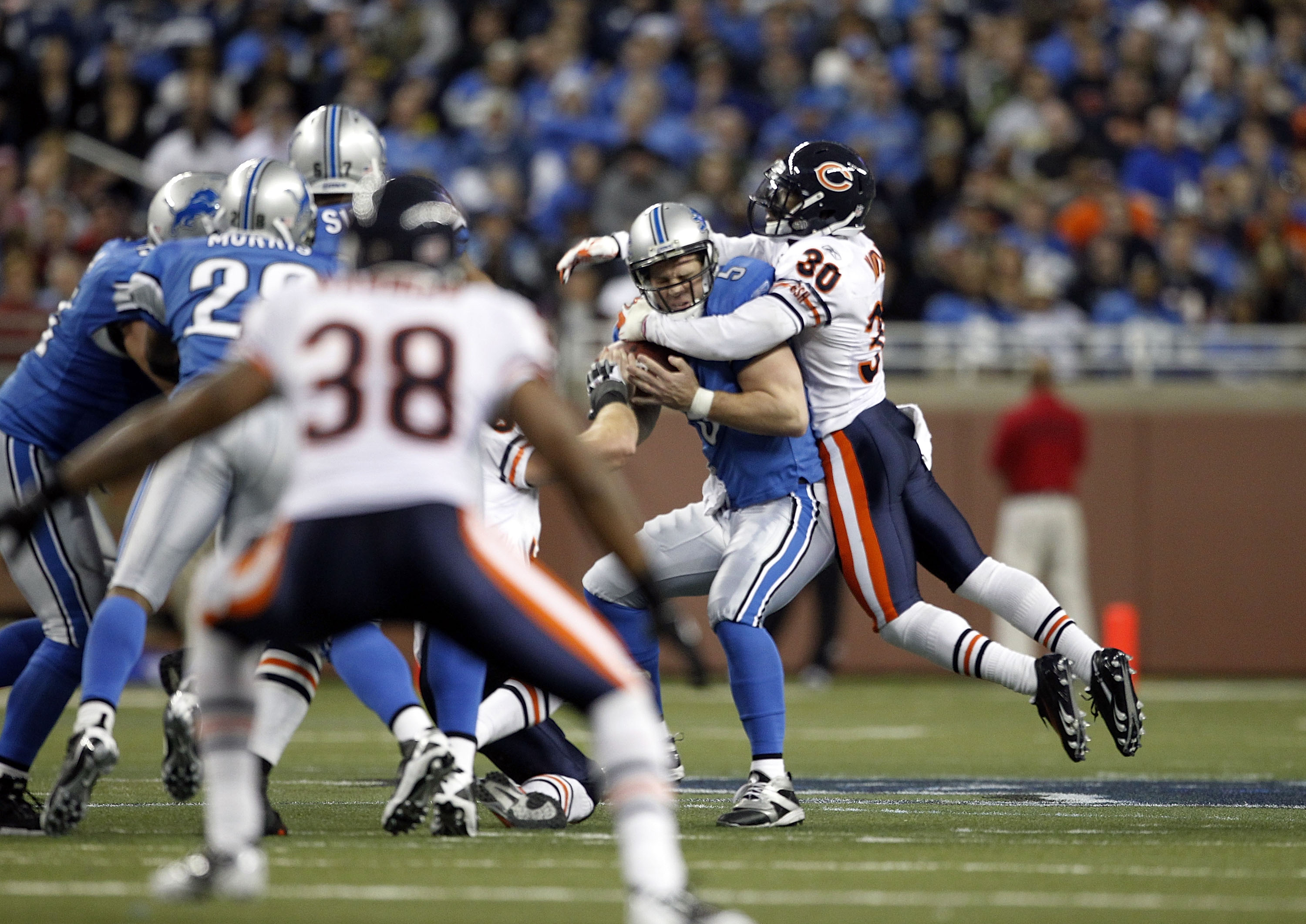 DETROIT - DECEMBER 05: Drew Stanton #5 of the Detroit Lions is sacked by D. J. Moore #30 of the Chicago Bears during the fourth quarter of the game at Ford Field on December 5, 2010 in Detroit, Michigan. The Bears defeated the Lions 24-20.  (Photo by Leon