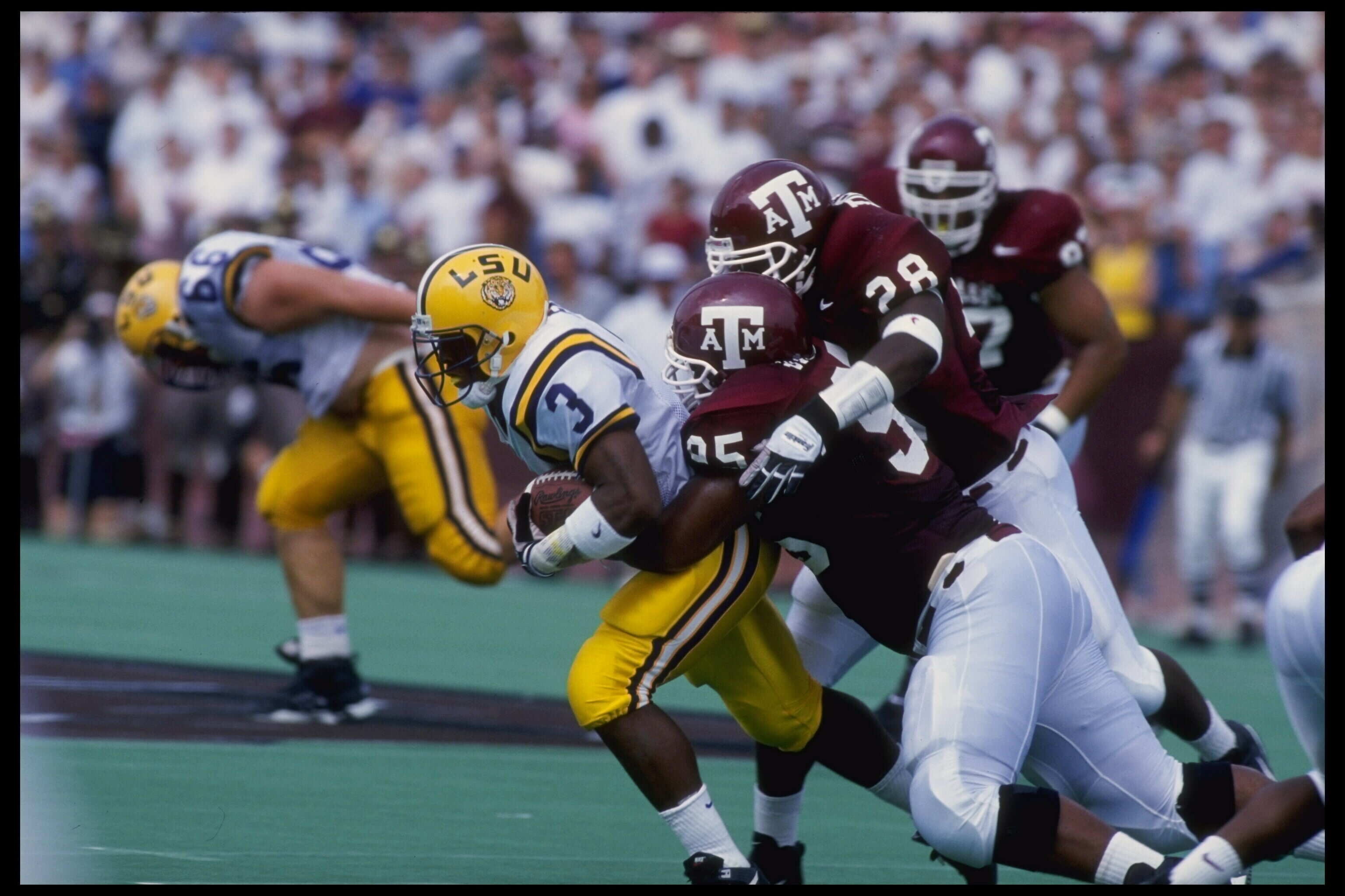 2 SEP 1995:  LSU RUNNING BACK KEVIN FAULK #3 IS TACKLED BY TEXAS A&M LINEBACKERS EDWARD JASPER #35 AND TRENT DRIVER #28 DURING LSU''S 33-17 LOSS AT KYLE FIELD IN COLLEGE STATION, TEXAS.  MANDATORY CREDIT:  ROBERT SEALE/ALLSPORT