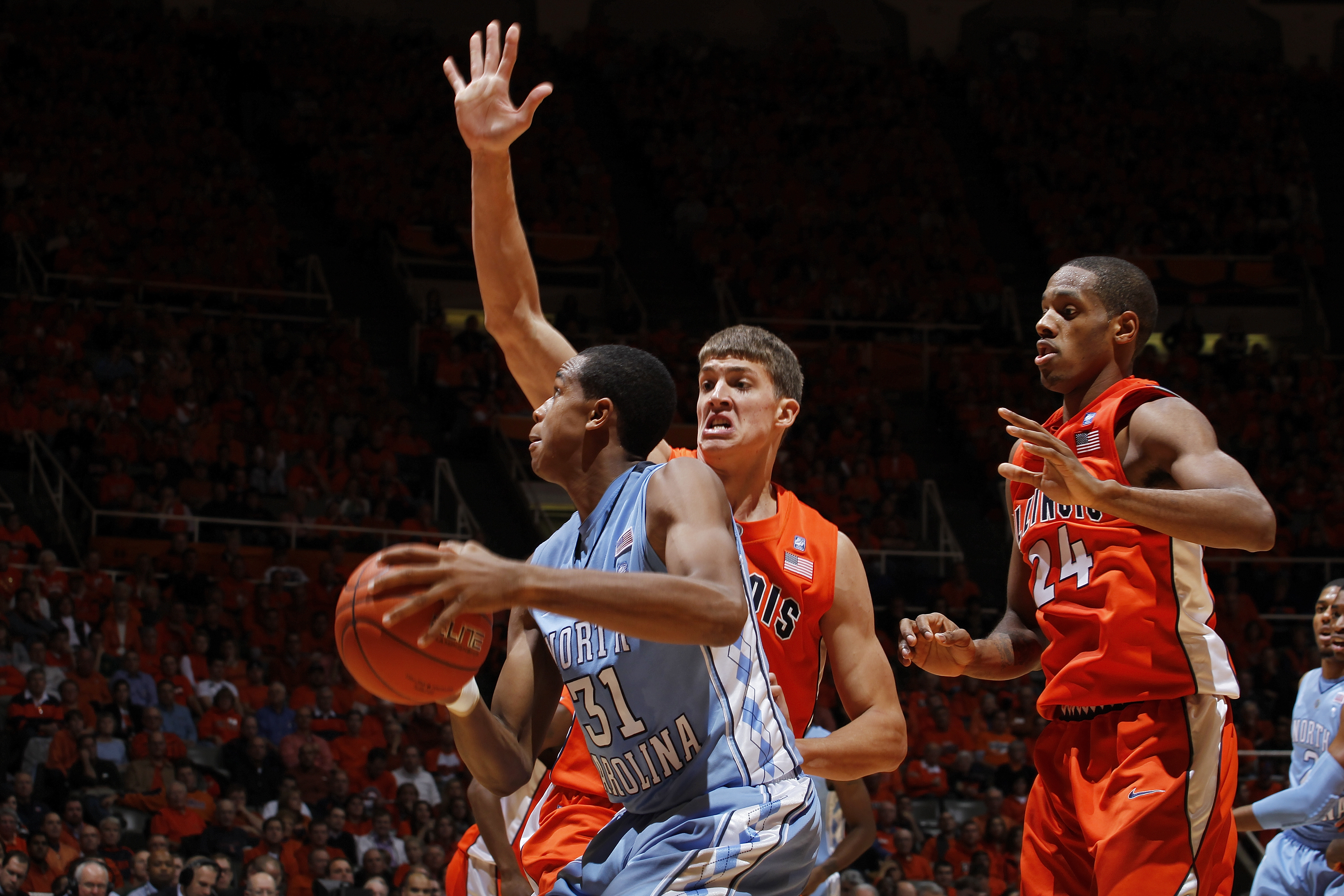 CHAMPAIGN, IL - NOVEMBER 30: Meyers Leonard #12 and Mike Davis #24 of the Illinois Fighting Illini defend against John Henson #31 of the North Carolina Tar Heels during the 2010 ACC/Big Ten Challenge at Assembly Hall on November 30, 2010 in Champaign, Ill