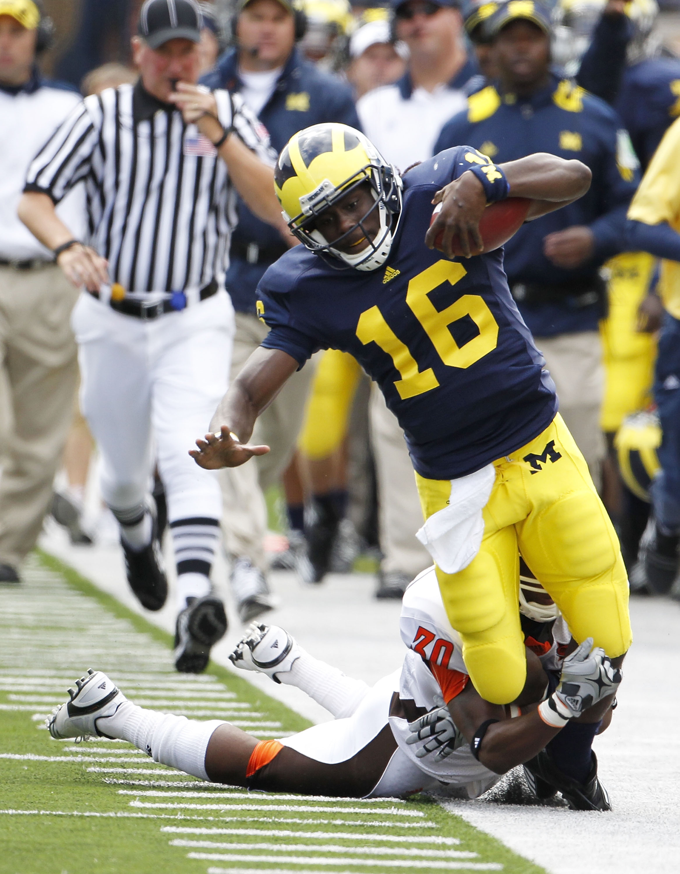 ANN ARBOR, MI - SEPTEMBER 25:  Cameron Truss #30 of Bowling Green tackles Denard Robison #16 of the Michigan Wolverines on September 25, 2010 at Michigan Stadium in Ann Arbor, Michigan. Robison left the game after this play with a reported leg injury.  (P