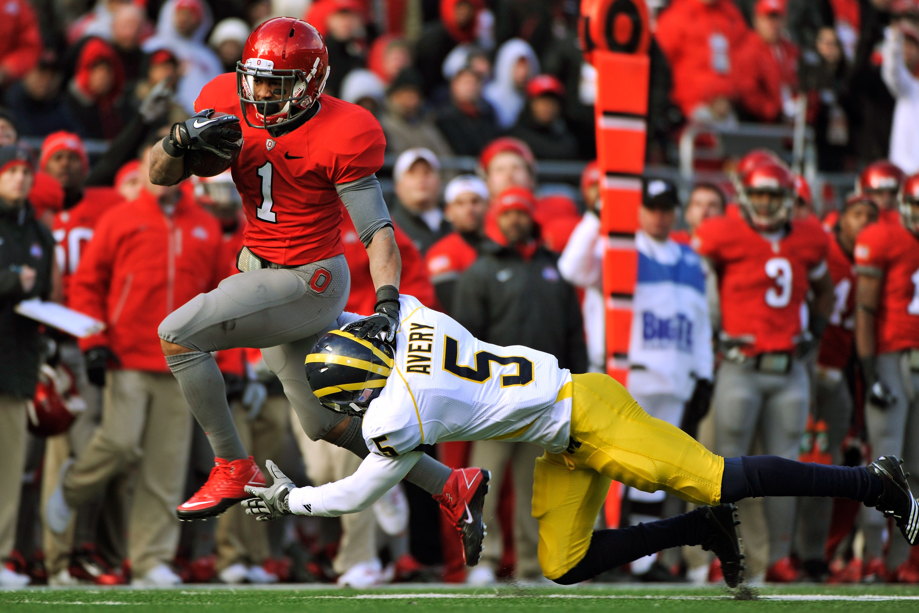 COLUMBUS, OH - NOVEMBER 27:  Dan Herron #1 of the Ohio State Buckeyes eludes the tackle attempt of Courtney Avery #5 of the Michigan Wolverines on his way to a 32-yard touchdown run in the third quarter at Ohio Stadium on November 27, 2010 in Columbus, Oh