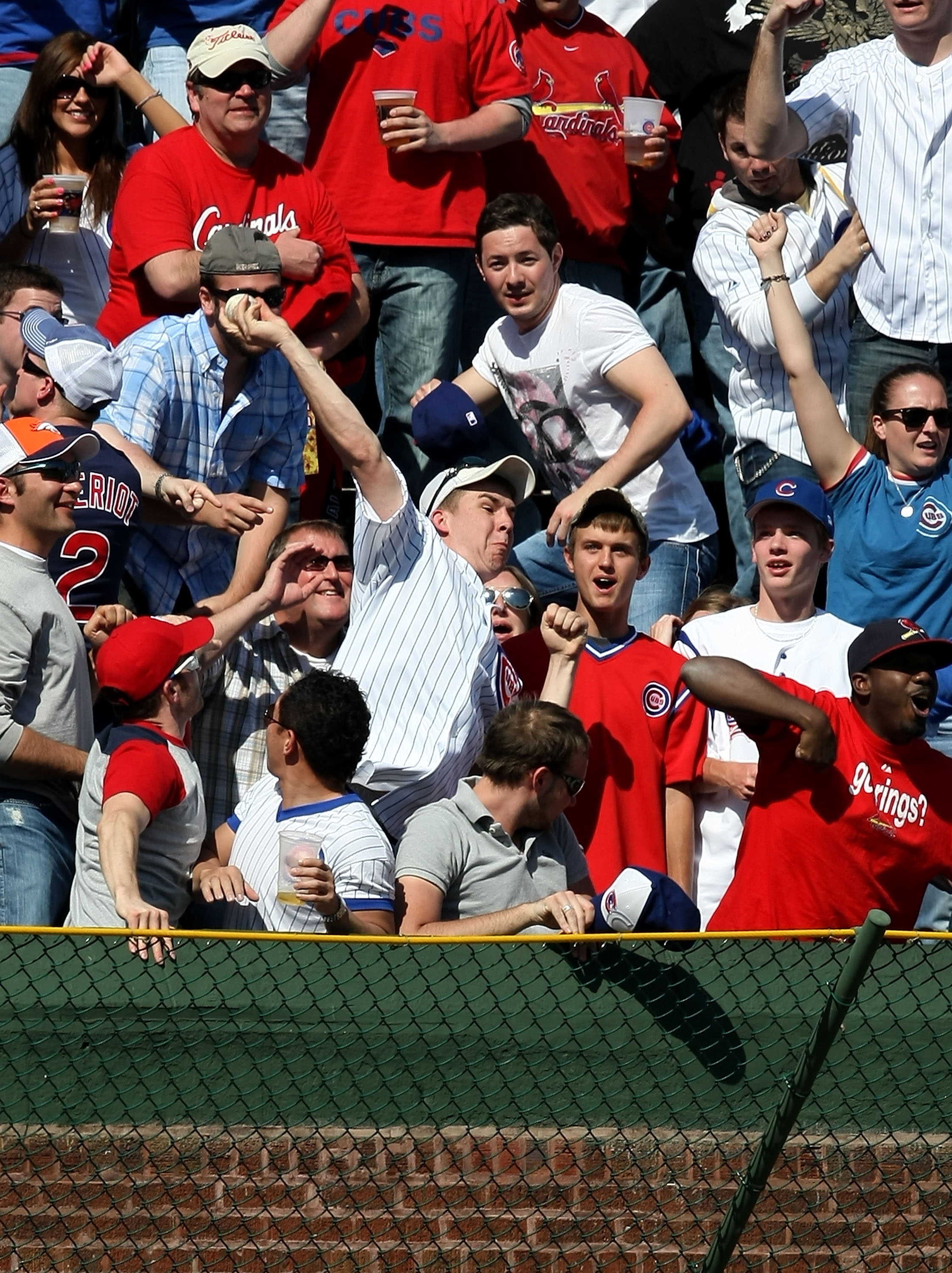 CHICAGO - APRIL 17: A Chicago Cubs fan in the left field bleachers throws back a home run ball hit by Ryan Ludwick of the St. Louis Cardinals in the 7th inning on April 17, 2009 at Wrigley Field in Chicago, Illinois. The Cubs defeated the Cardinals 8-7. (