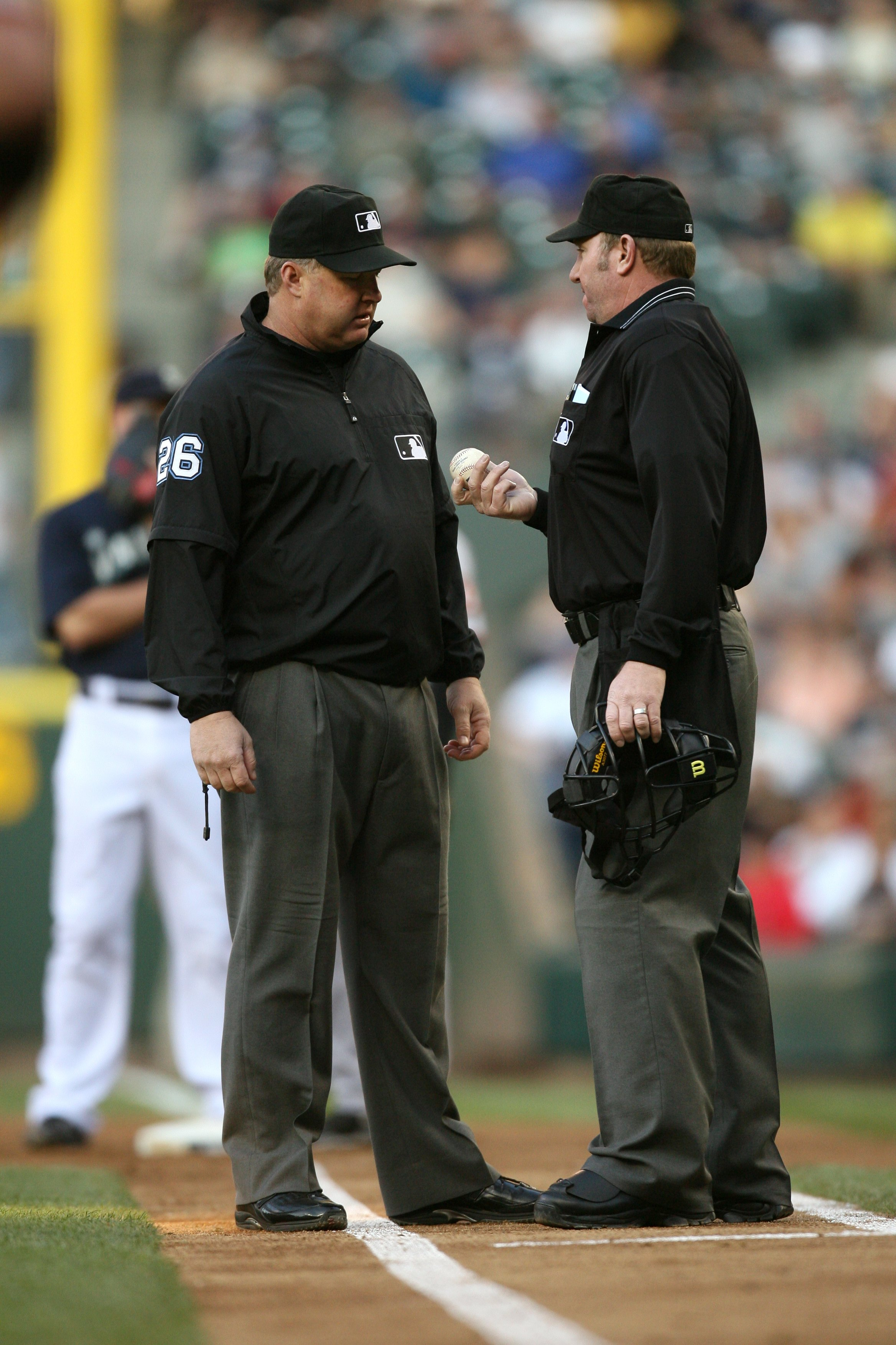SEATTLE - MAY 22:  MLB home plate umpire Brian Runge and first base umpire Bill Miller #26 confer near the infield foul line during the game between the San Francisco Giants  and the Seattle Mariners on May 22, 2009 in Seattle, Washington. The Mariners de