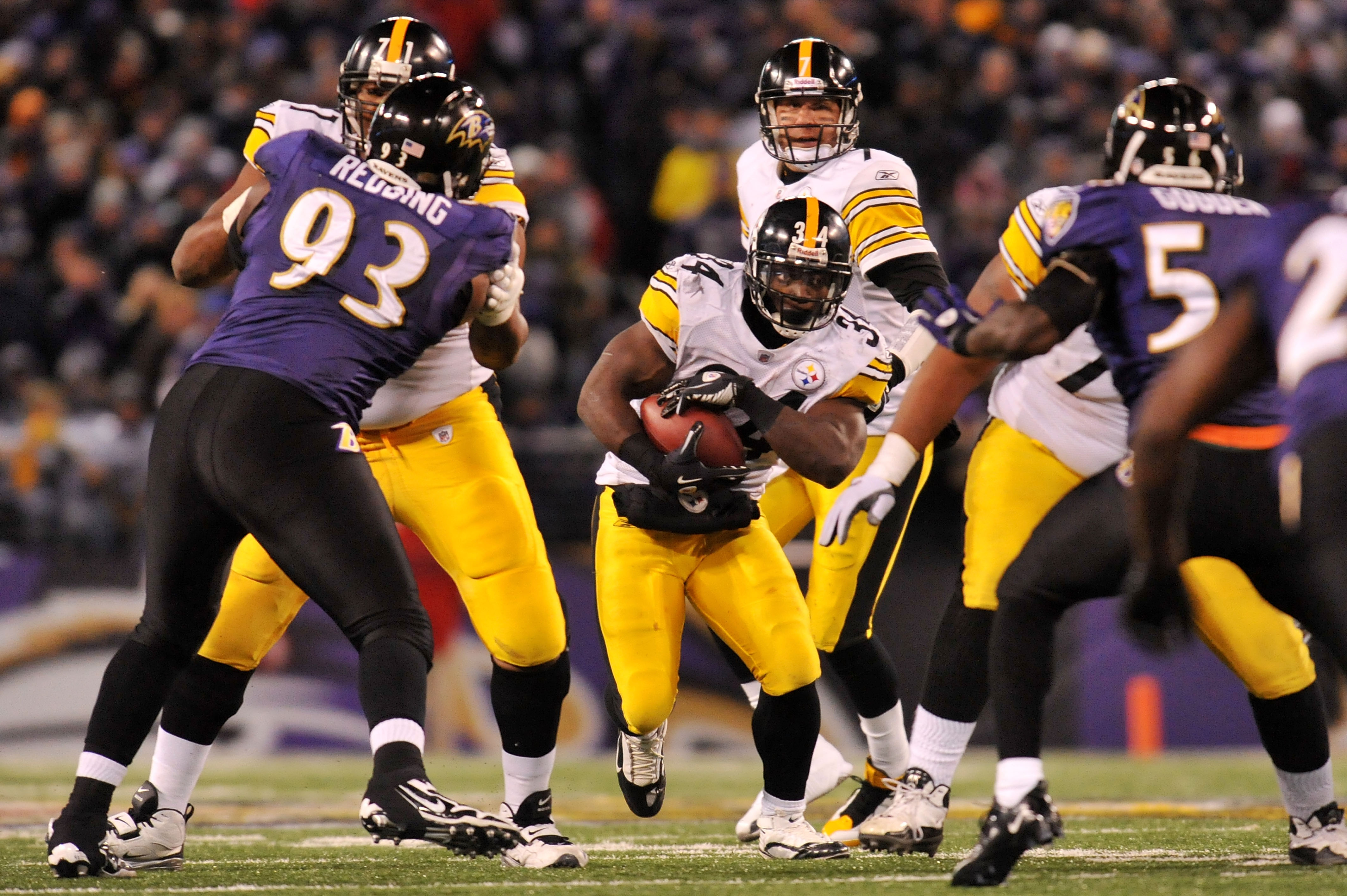 BALTIMORE, MD - DECEMBER 05:  Running back Rashard Mendenhall #34 of the Pittsburgh Steelers runs the ball against defensive end Cory Redding #93 and linebacker Tavares Gooden #56 of the Baltimore Ravens during the third quarter of the game at M&T Bank St